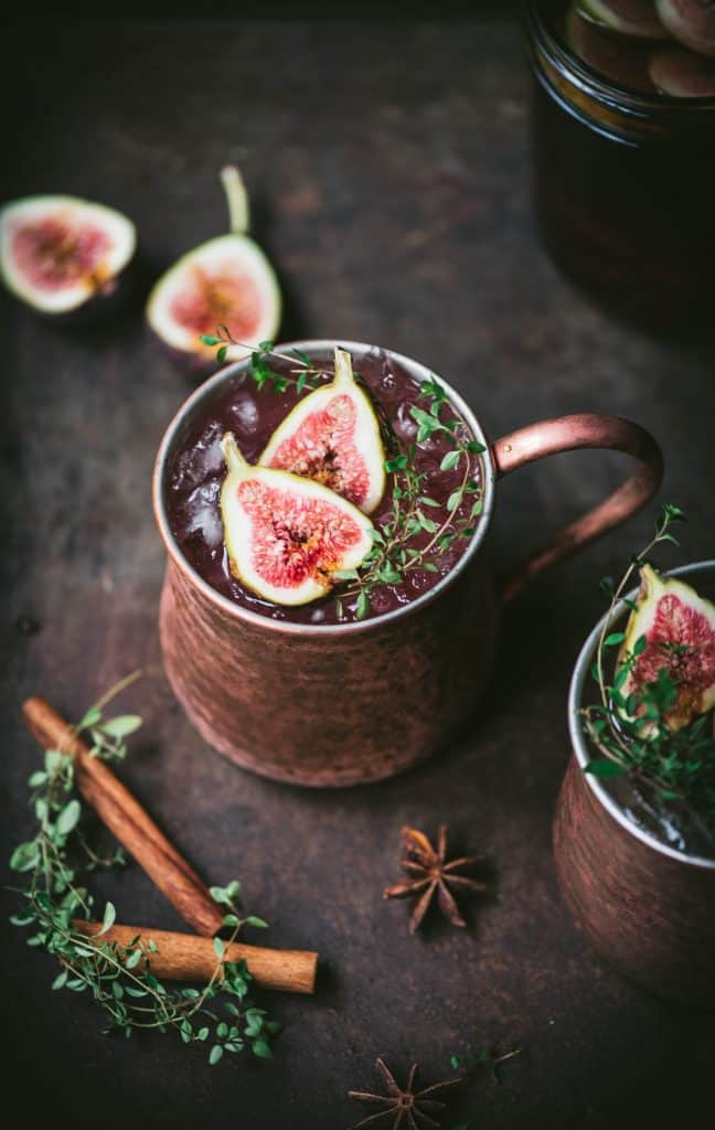 Side view of fig moscow mule in copper mug with cinnamon sticks and fresh thyme
