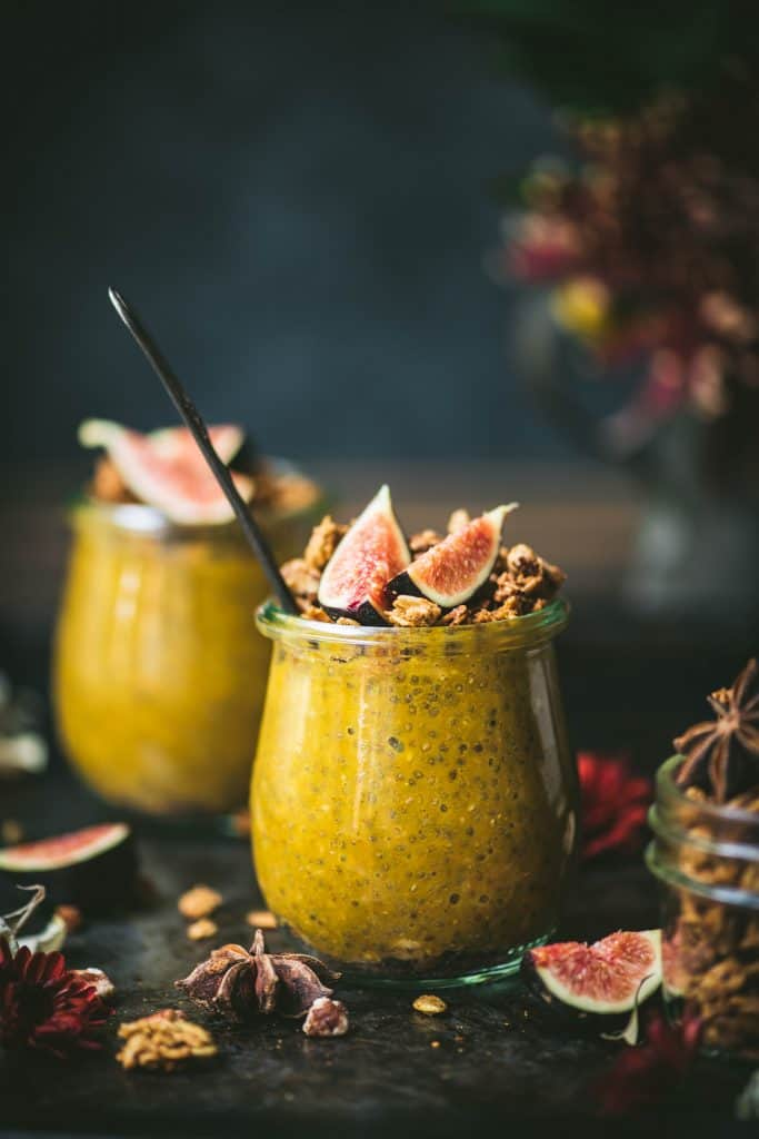 Side view of pumpkin chia pudding in a small glass jar topped with fresh figs and granola. Styled on a dark, rustic background with fall flowers in background
