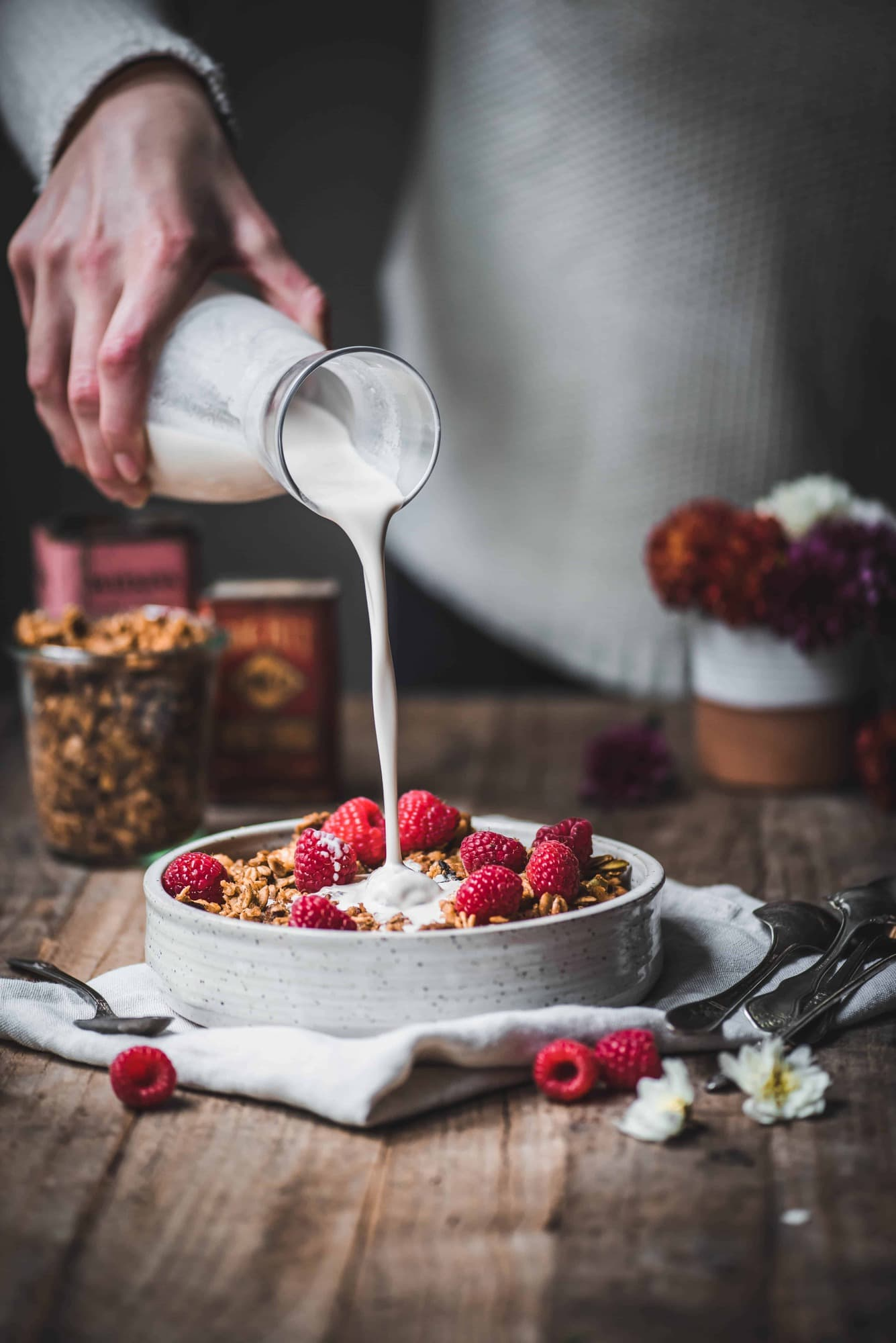 Pouring milk over granola with fresh raspberries on a rustic wood table