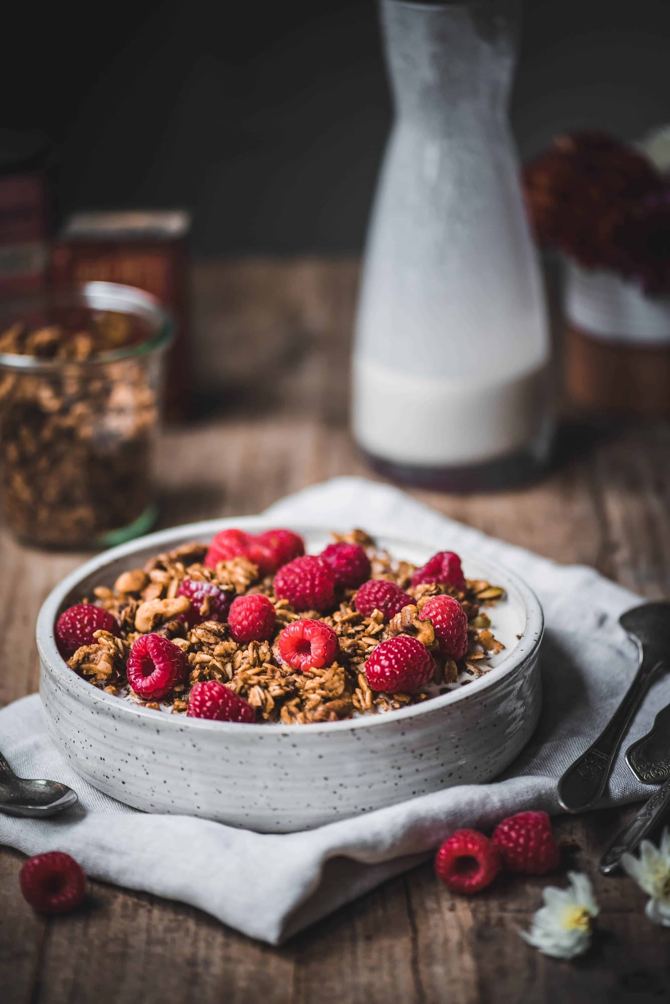 Side view of pumpkin spice granola with milk and fresh raspberries in a white bowl on rustic wood table