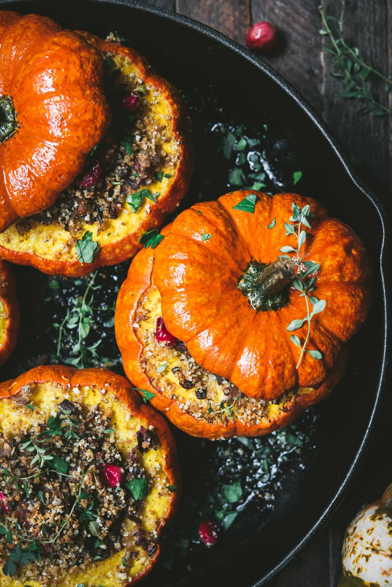 Close up view of Stuffed Mini Pumpkins with Wild Rice and Mushrooms in a cast iron skillet