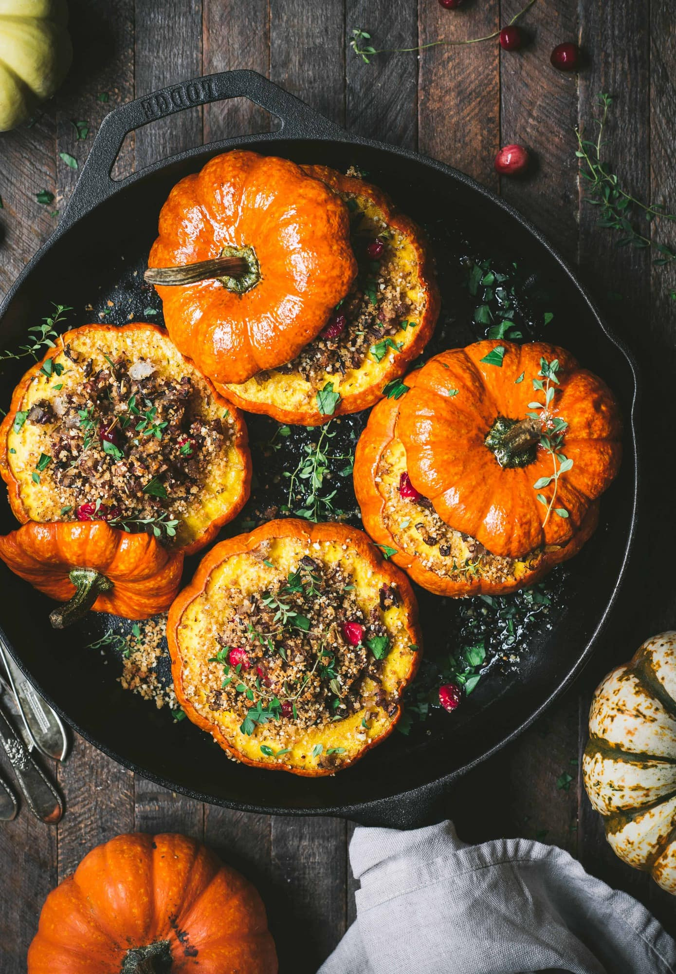 Overhead view of 4 Stuffed Mini Pumpkins with Wild Rice and Mushrooms in a cast iron skillet