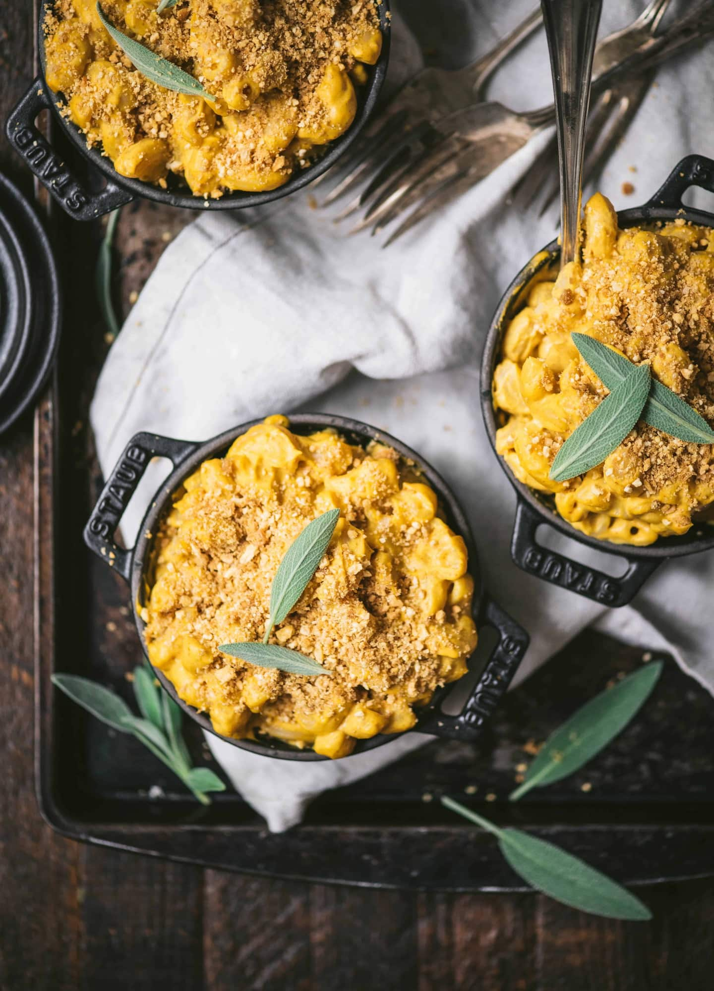 Overhead of vegan pumpkin mac and cheese in 3 mini Staub black cast iron coquettes