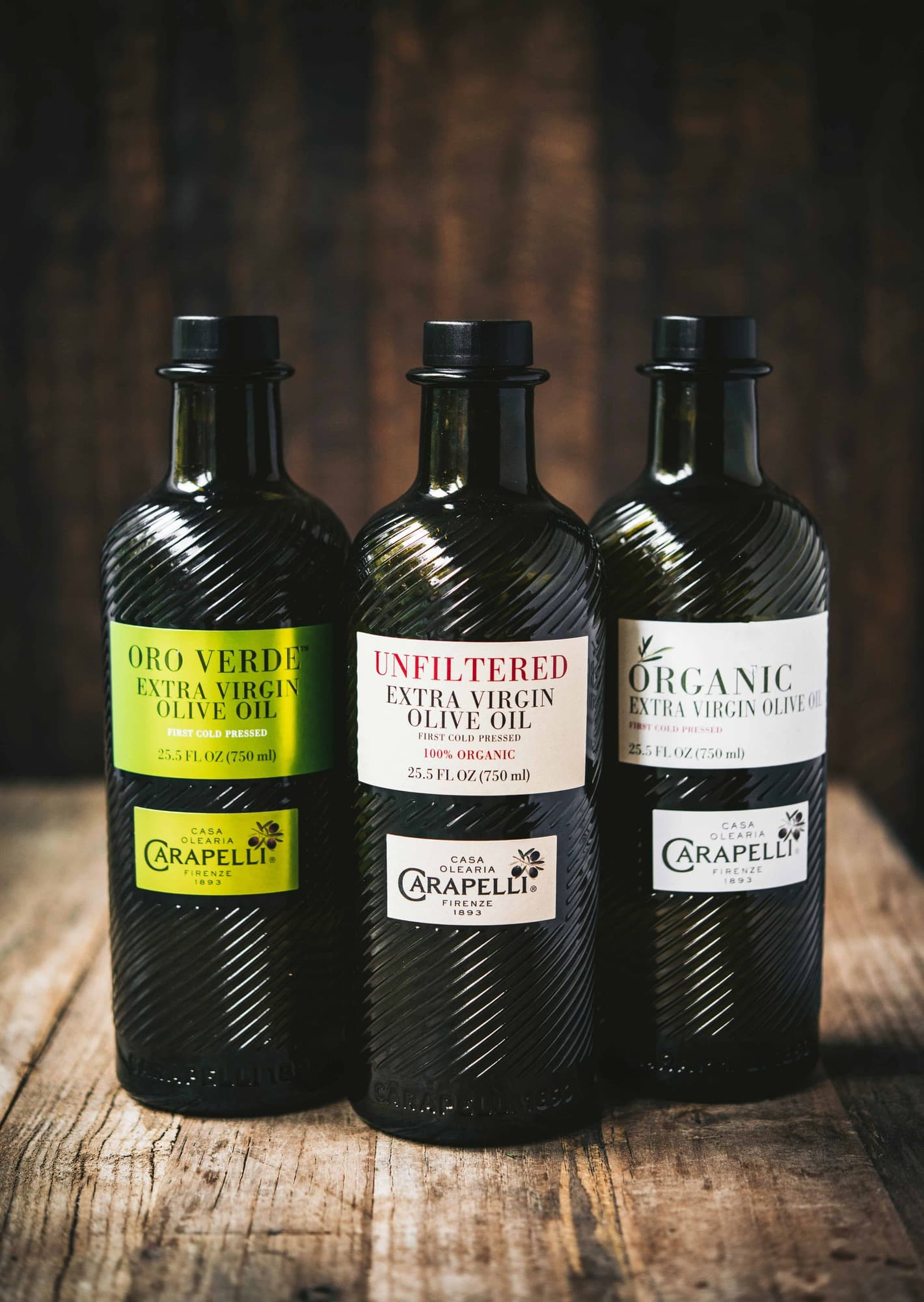 Three bottles of Carapelli Olive Oil on rustic wood background