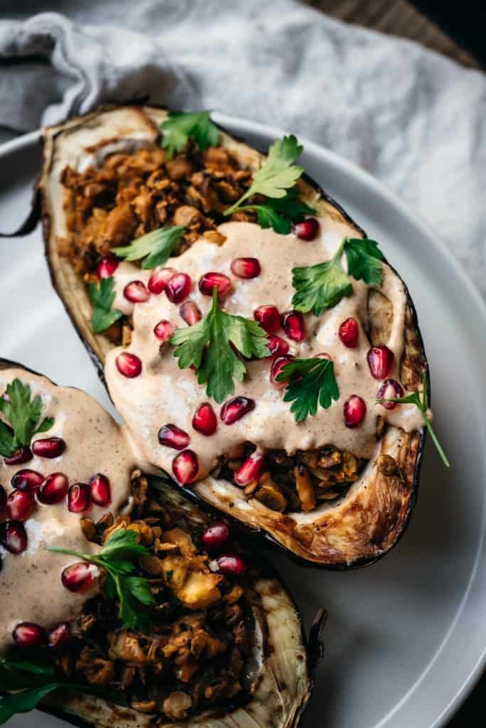 Side view of Stuffed roasted eggplants drizzled with tahini and pomegranate on a white plate