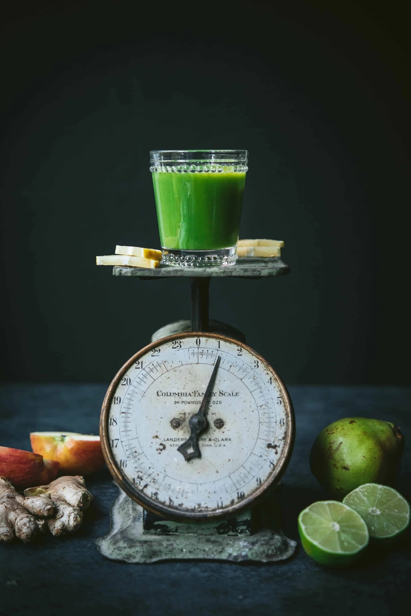 Small glass of green juice atop an antique green scale