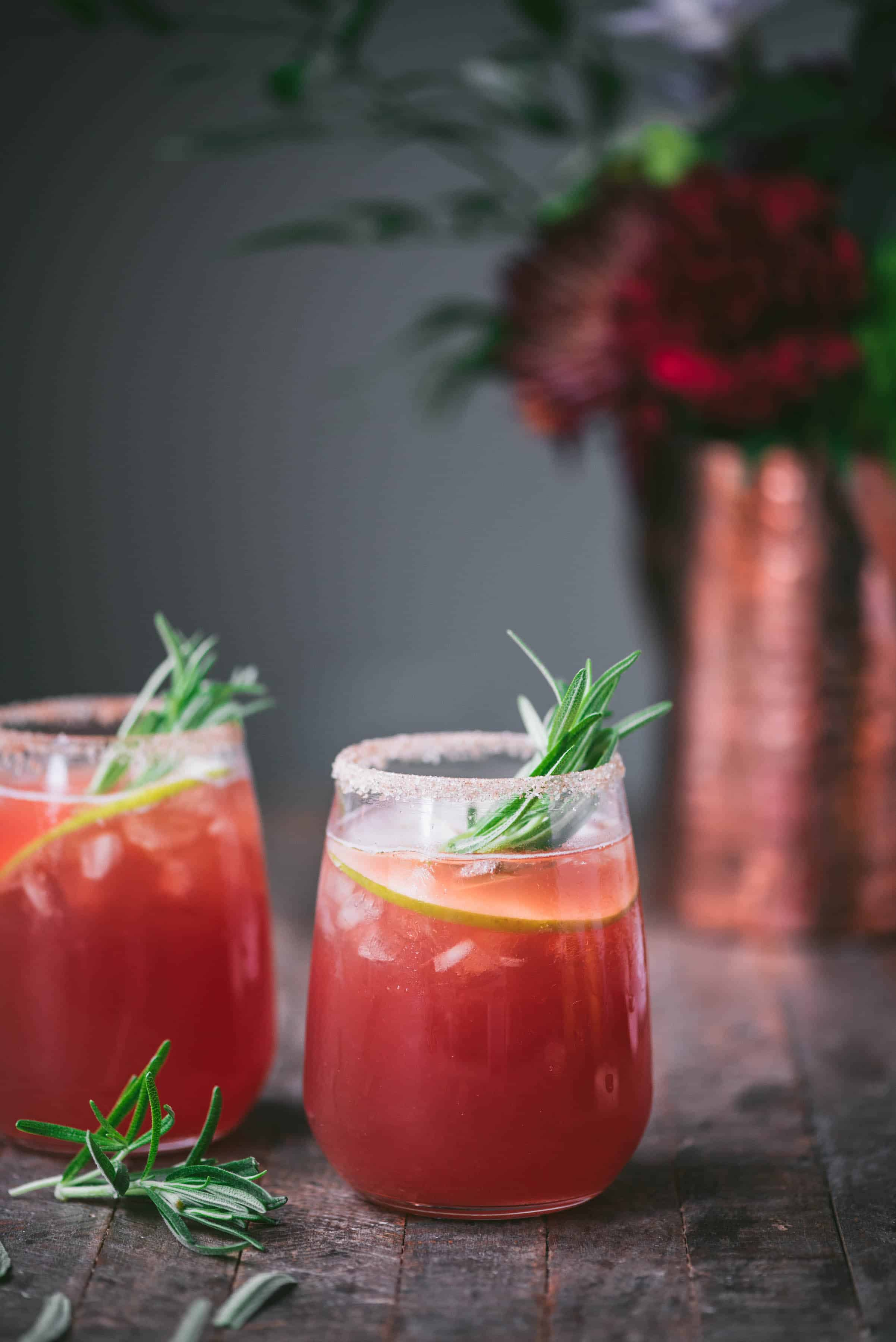Side view of apple cider cranberry margarita with rosemary and apple garnish on rustic wood background with flowers in copper vase