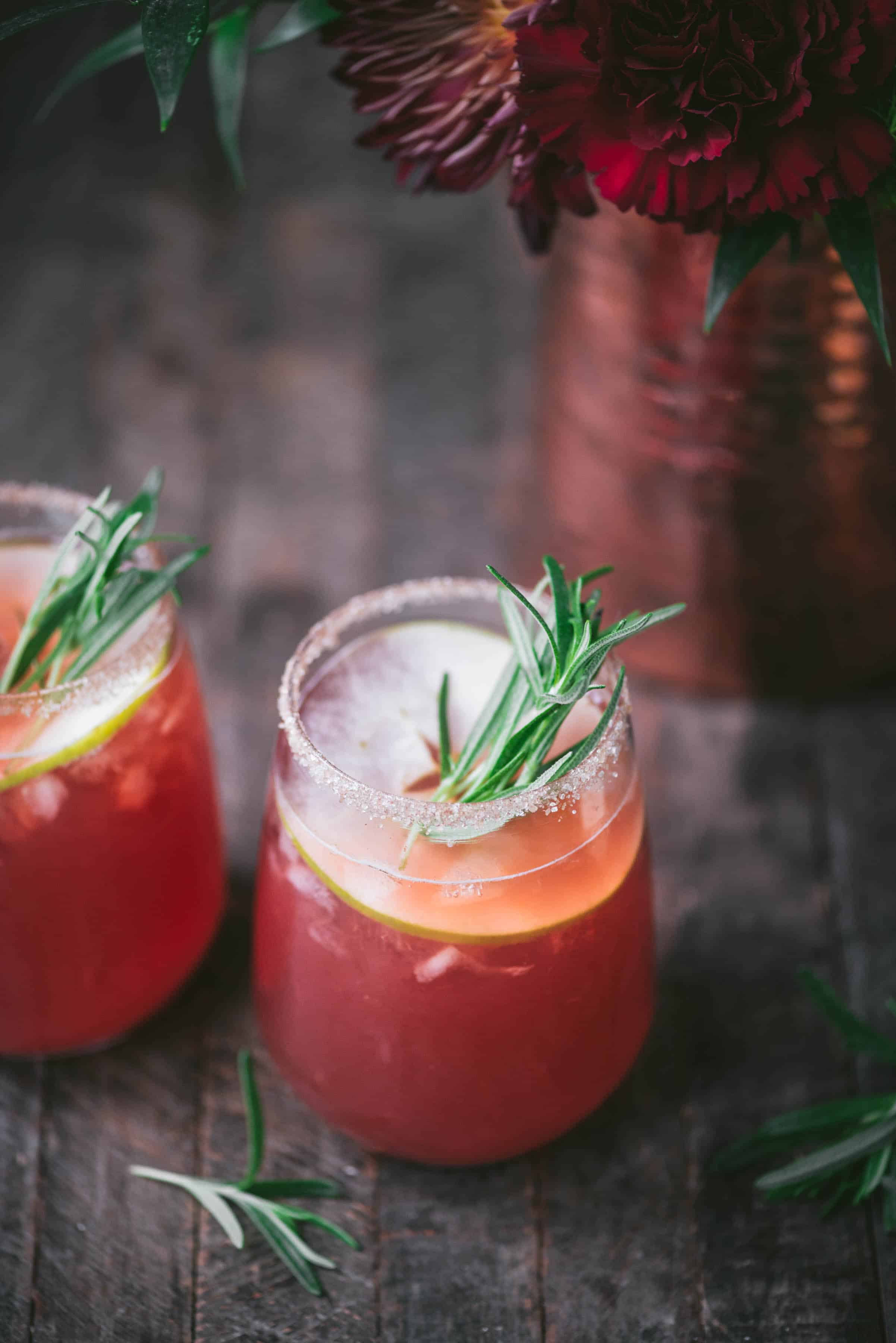 45 degree angle of apple cider cranberry margarita with rosemary and apple garnish on rustic wood background
