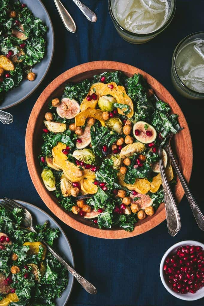 Large bowl of kale salad with fall roasted vegetables, tahini dressing and a bowl of pomegranate seeds