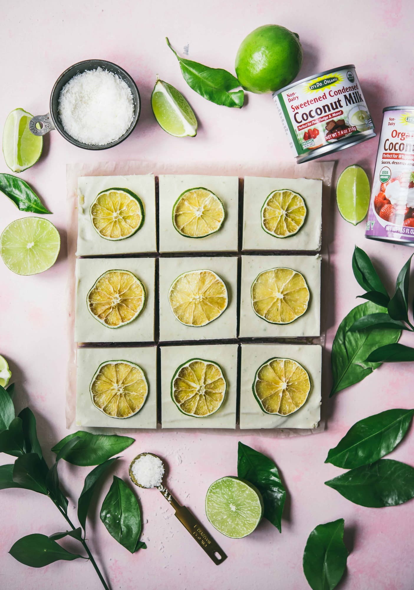 Overhead of coconut lime cheesecake bars on a pink background
