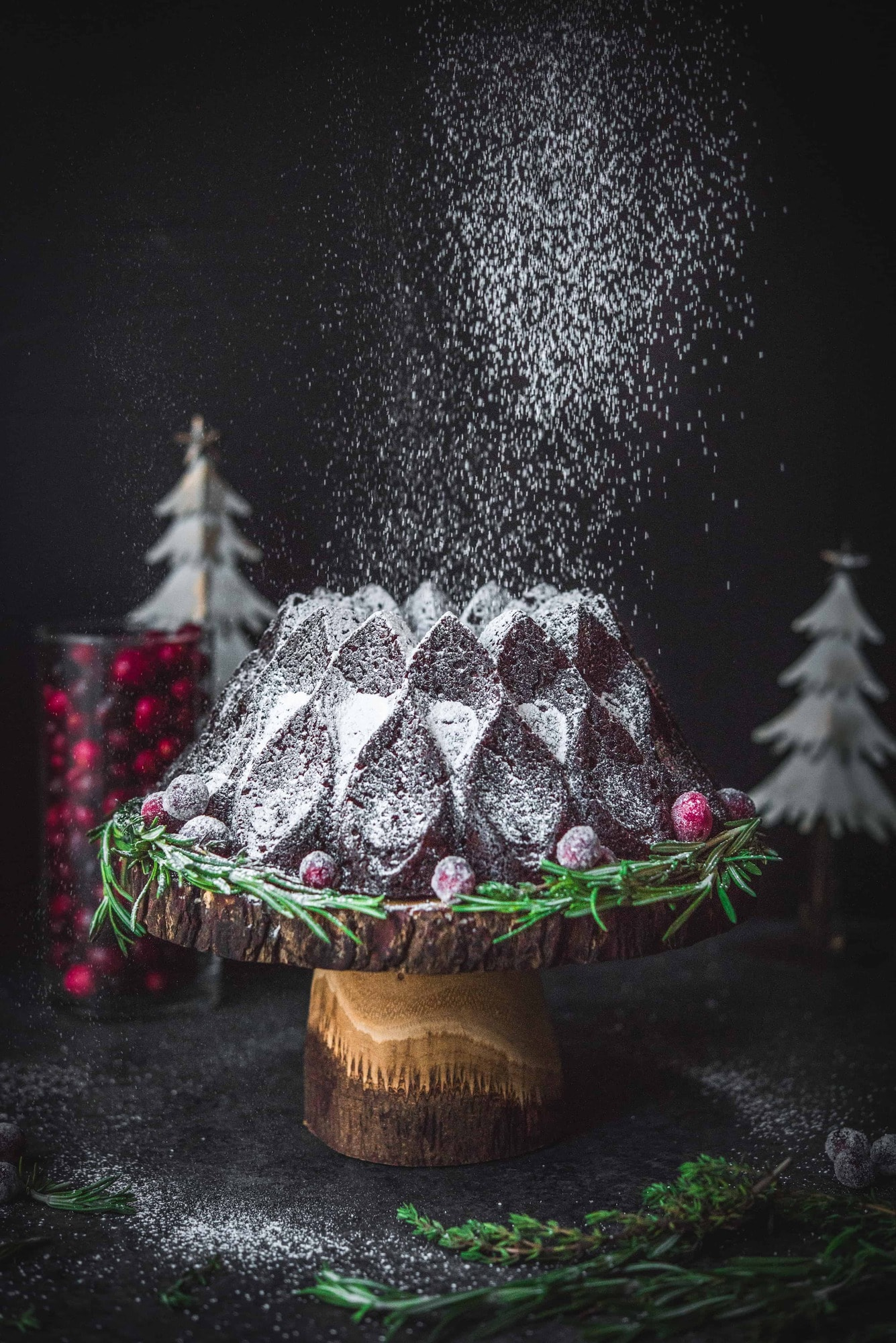 Action shot of powdered sugar falling on chocolate gingerbread bundt cake
