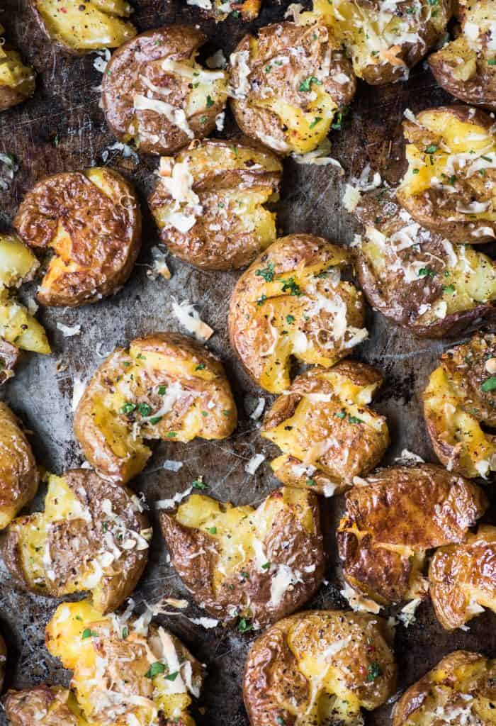 Close up overhead of crispy smashed potatoes with vegan parmesan and herbs