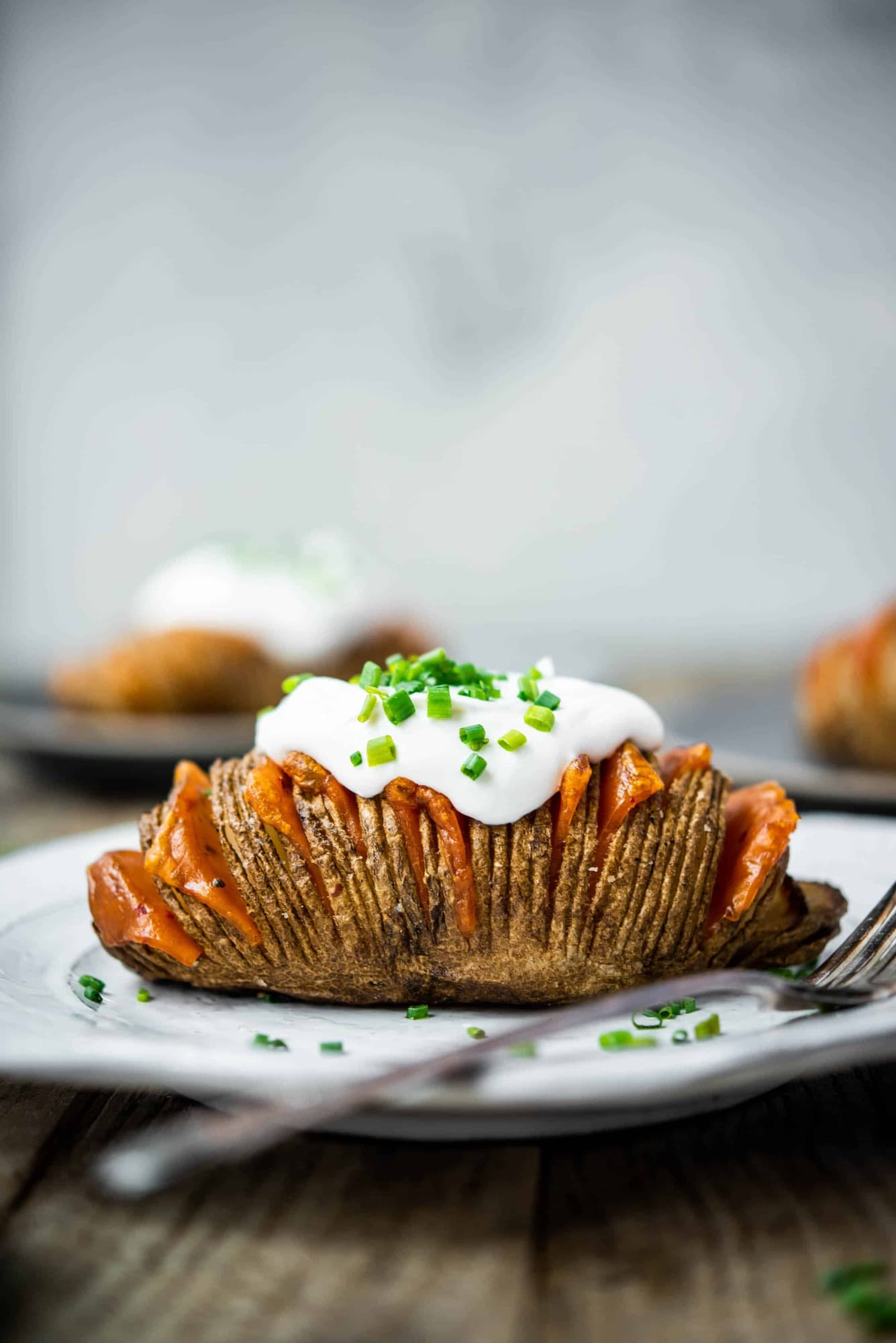 Side view of vegan cheesy hasselback potato on a white plate