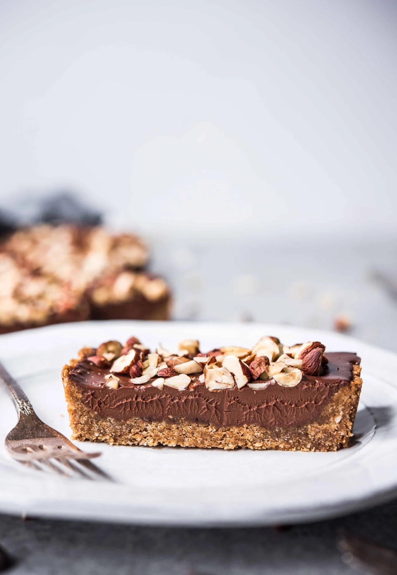 Side view of slice of chocolate hazelnut ganache tart on a white plate with fork