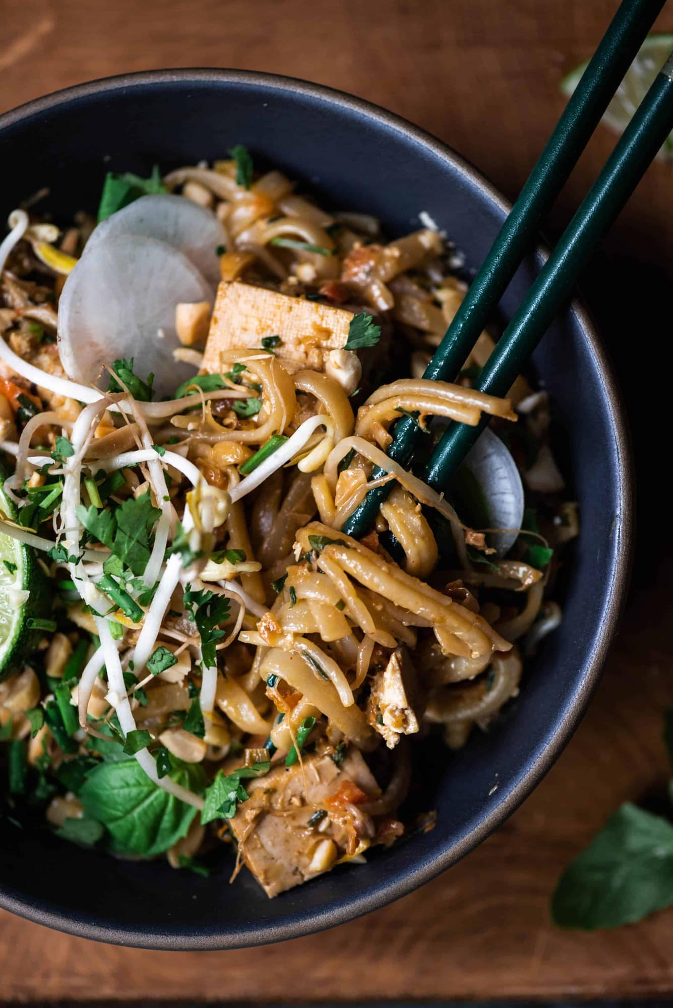 Close up of vegan pad thai noodles wrapped around chopsticks in a dark grey bowl