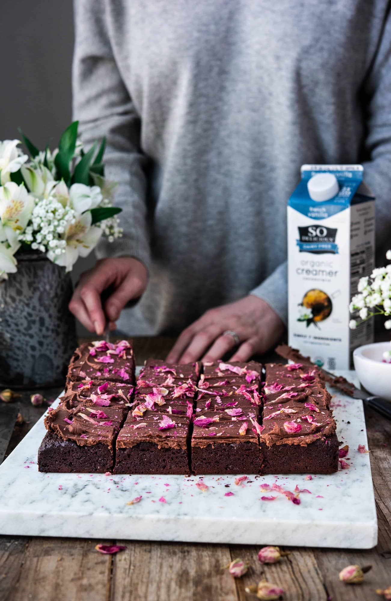 Side view of person cutting chocolate ganache brownies with rose petals