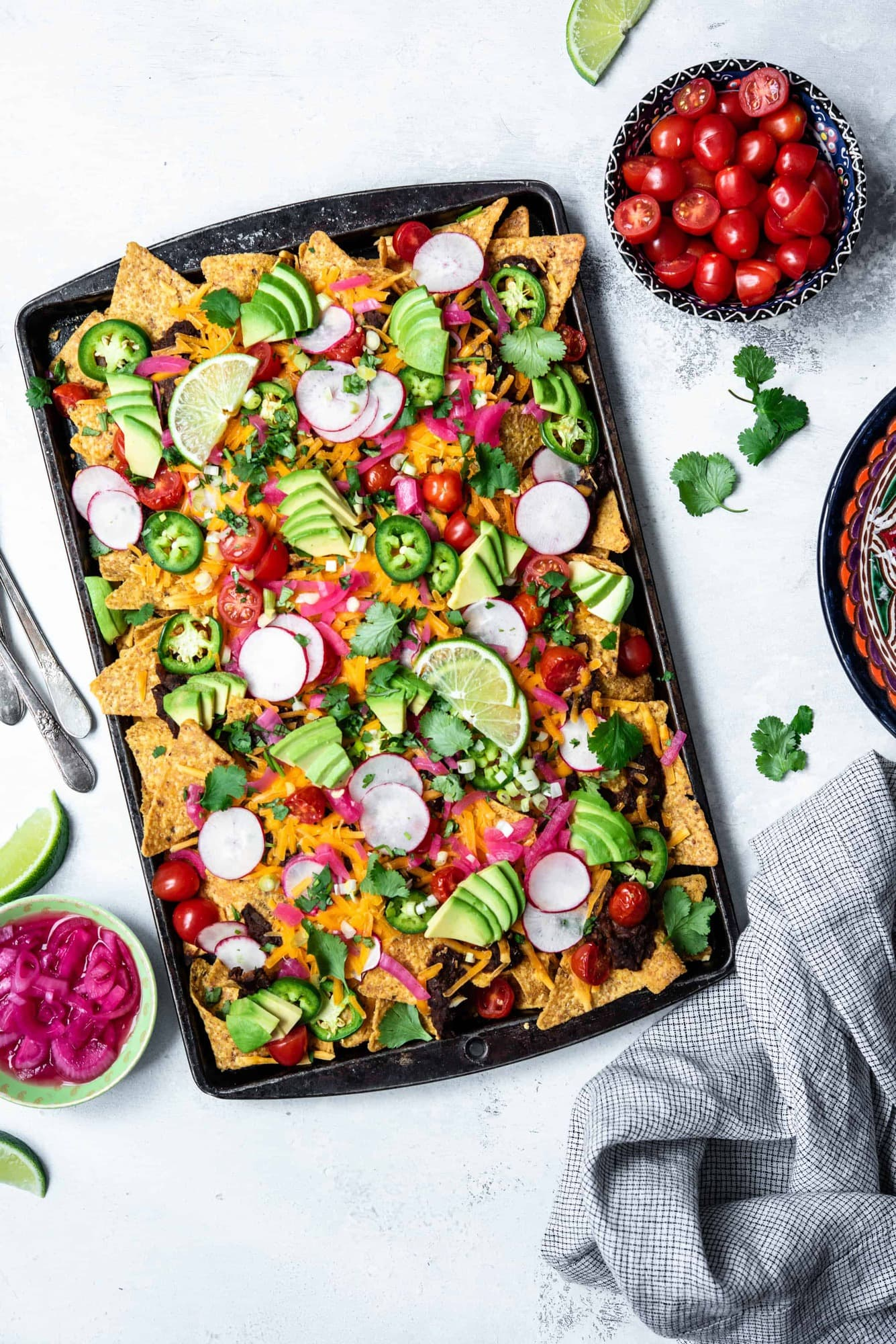 Overhead view of loaded black bean nachos on a sheet pan with avocado, cheese, pickled onion, tomatoes and jalapeño