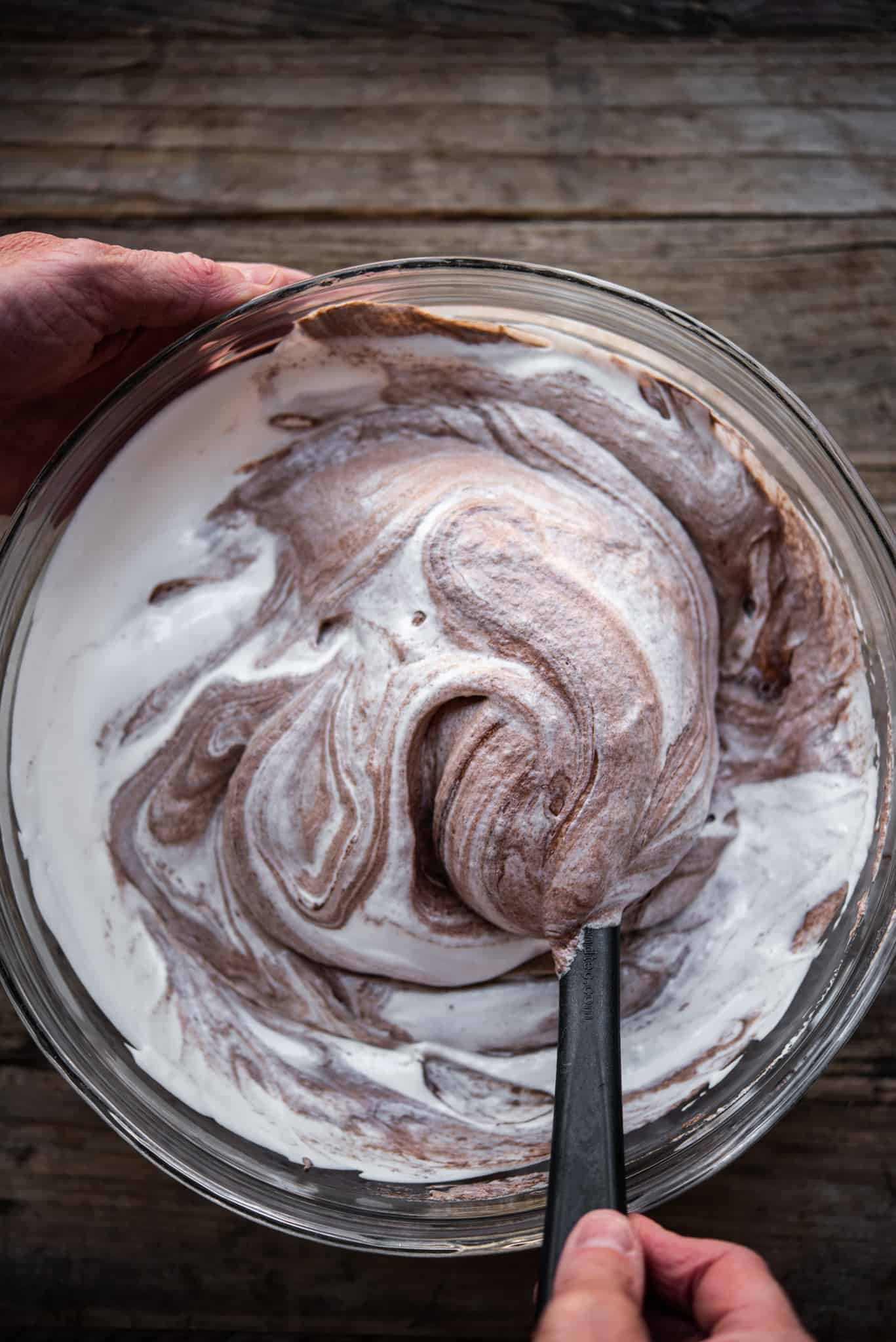 Person folding chocolate into whipped aquafaba to make mousse