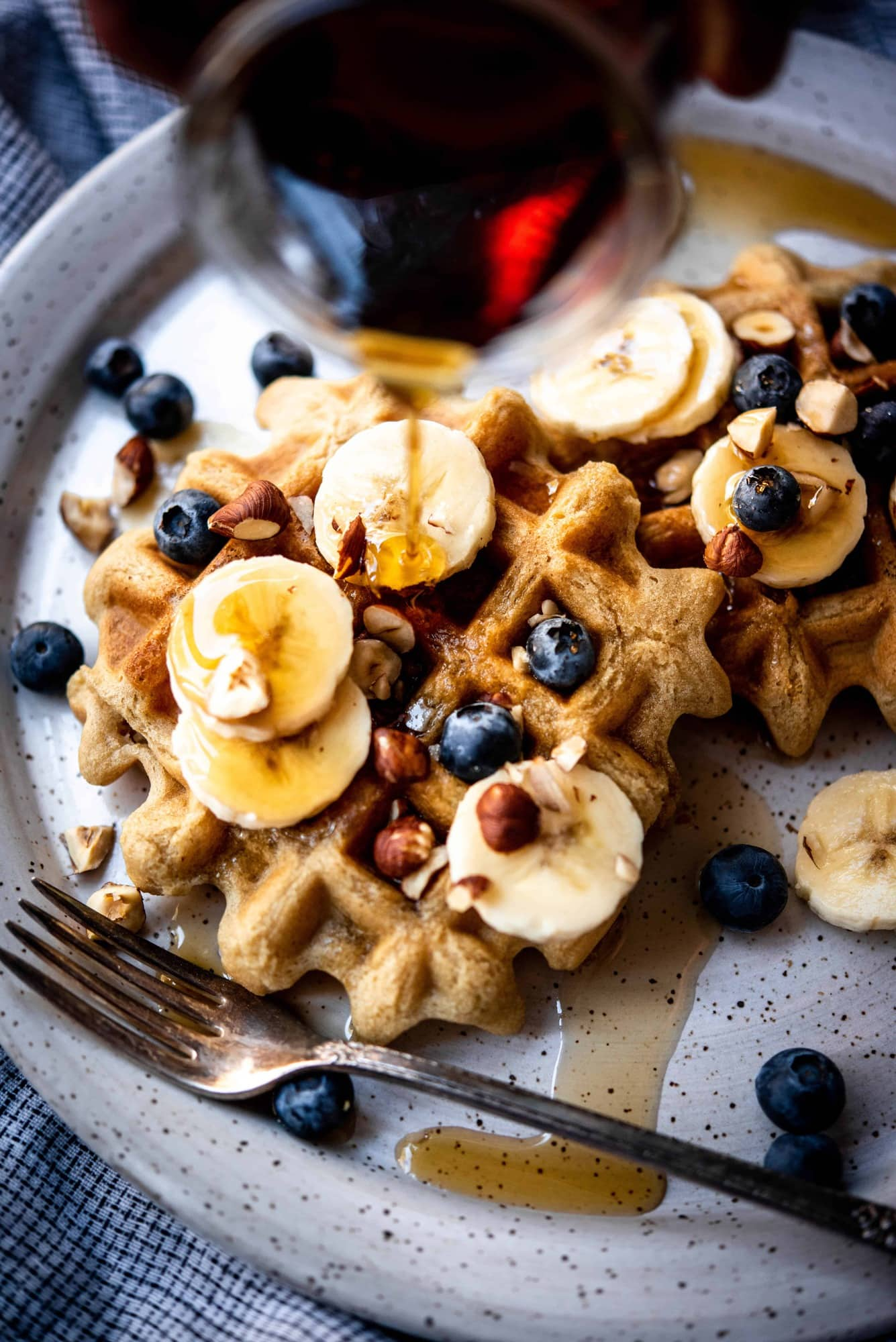 Close up view of pouring maple syrup on waffles topped with bananas and blueberries