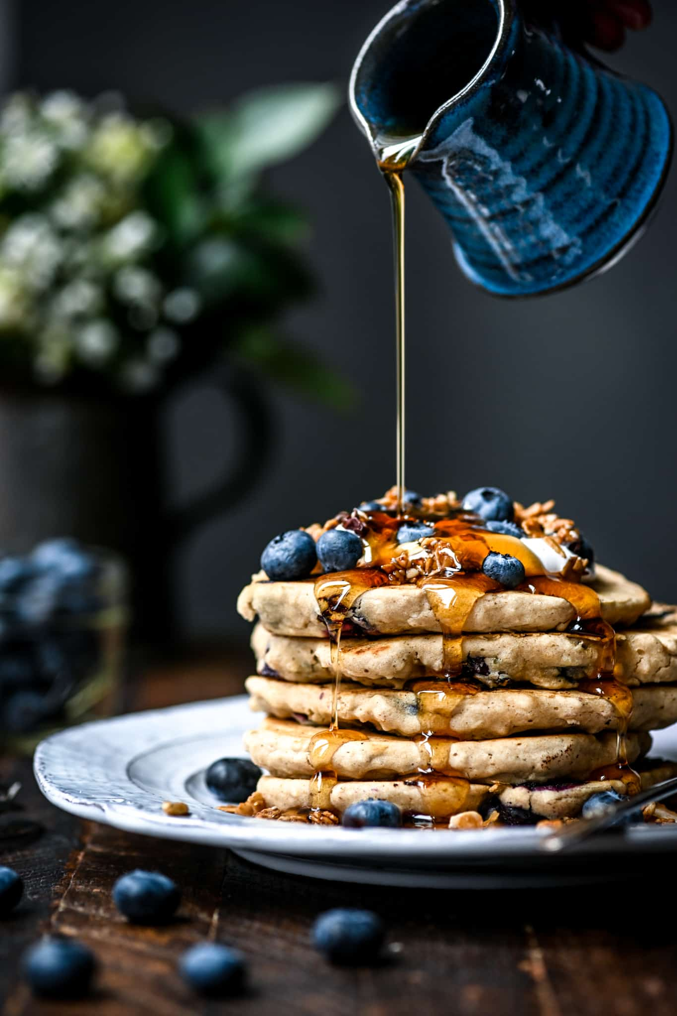 Side view of pouring maple syrup onto a stack of gluten free vegan blueberry pancakes with granola and fresh blueberries on a white plate