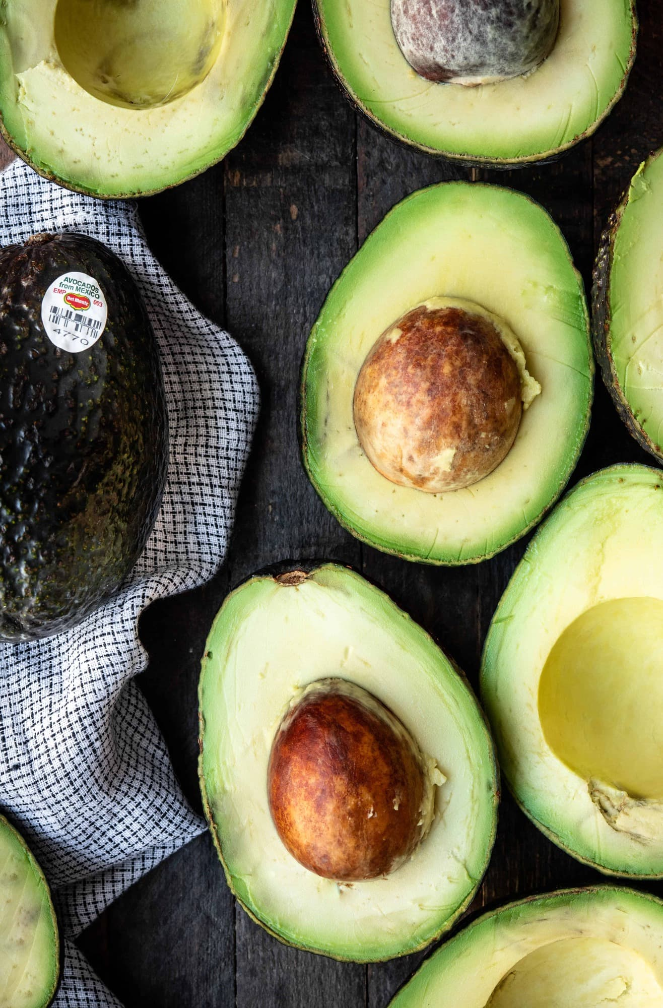 Overhead view of multiple avocados cut in half on a wood background
