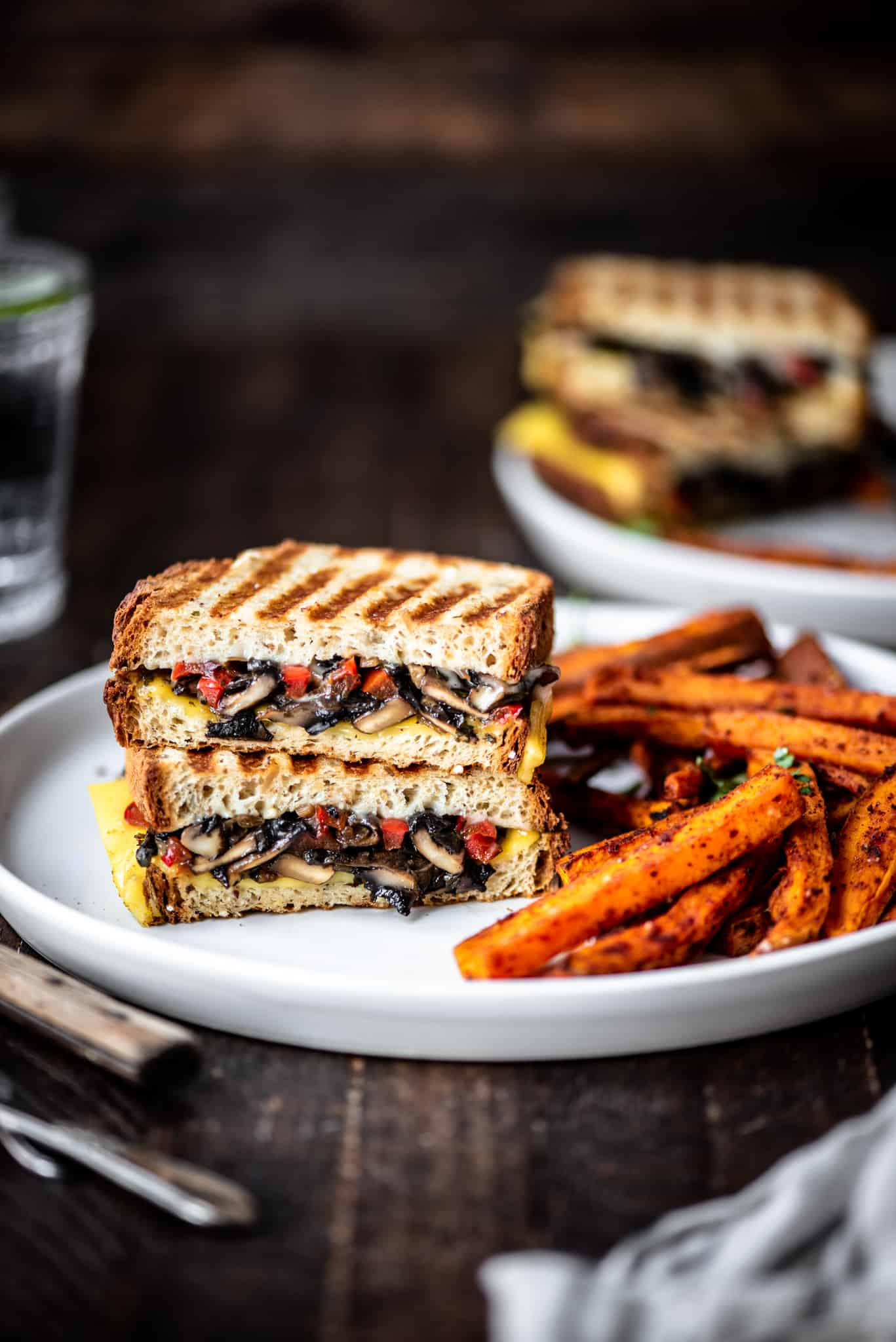 Side view of gluten free mushroom panini on a white plate with sweet potato fries