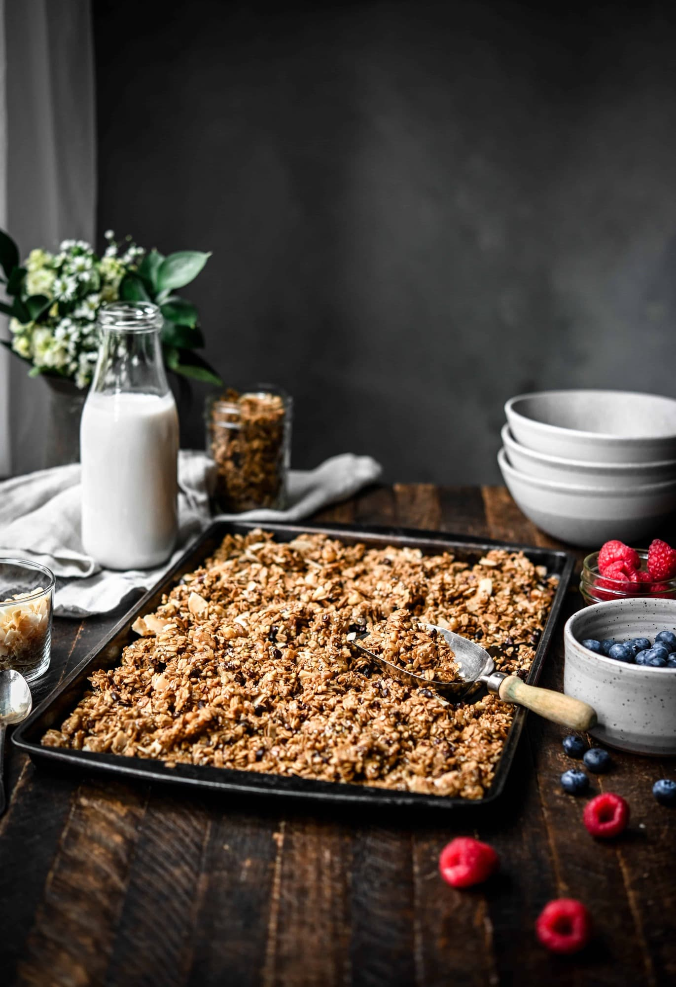 Side view of a baking sheet with granola and a scoop on a wood table with greenery in background