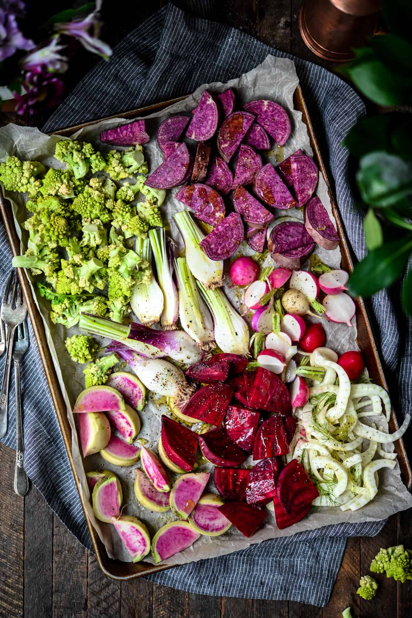 Overhead of sheet pan with uncooked purple, pink and green vegetables