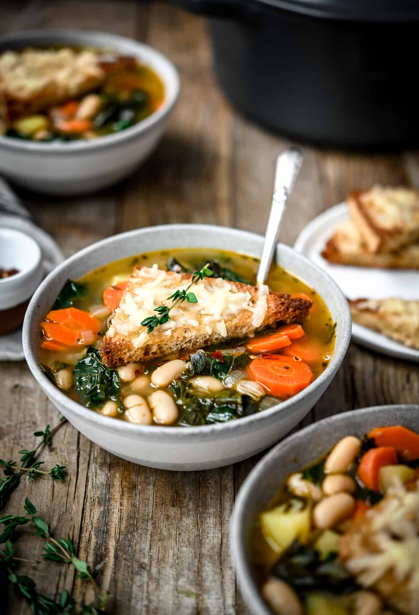 Side view of one-pot white bean kale soup in a grey bowl on a wood table