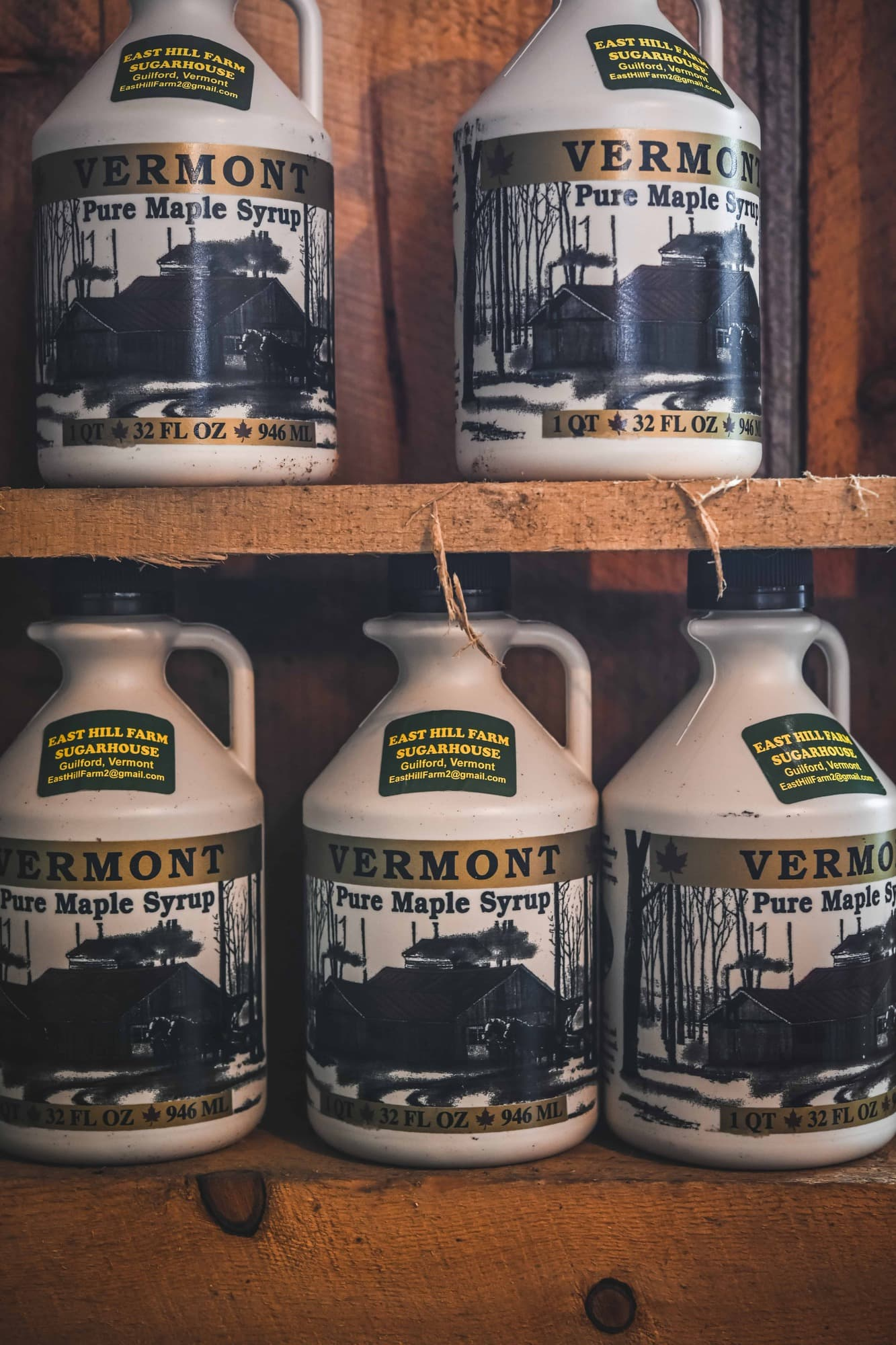 Close up of large jugs of Vermont maple syrup on wood shelves