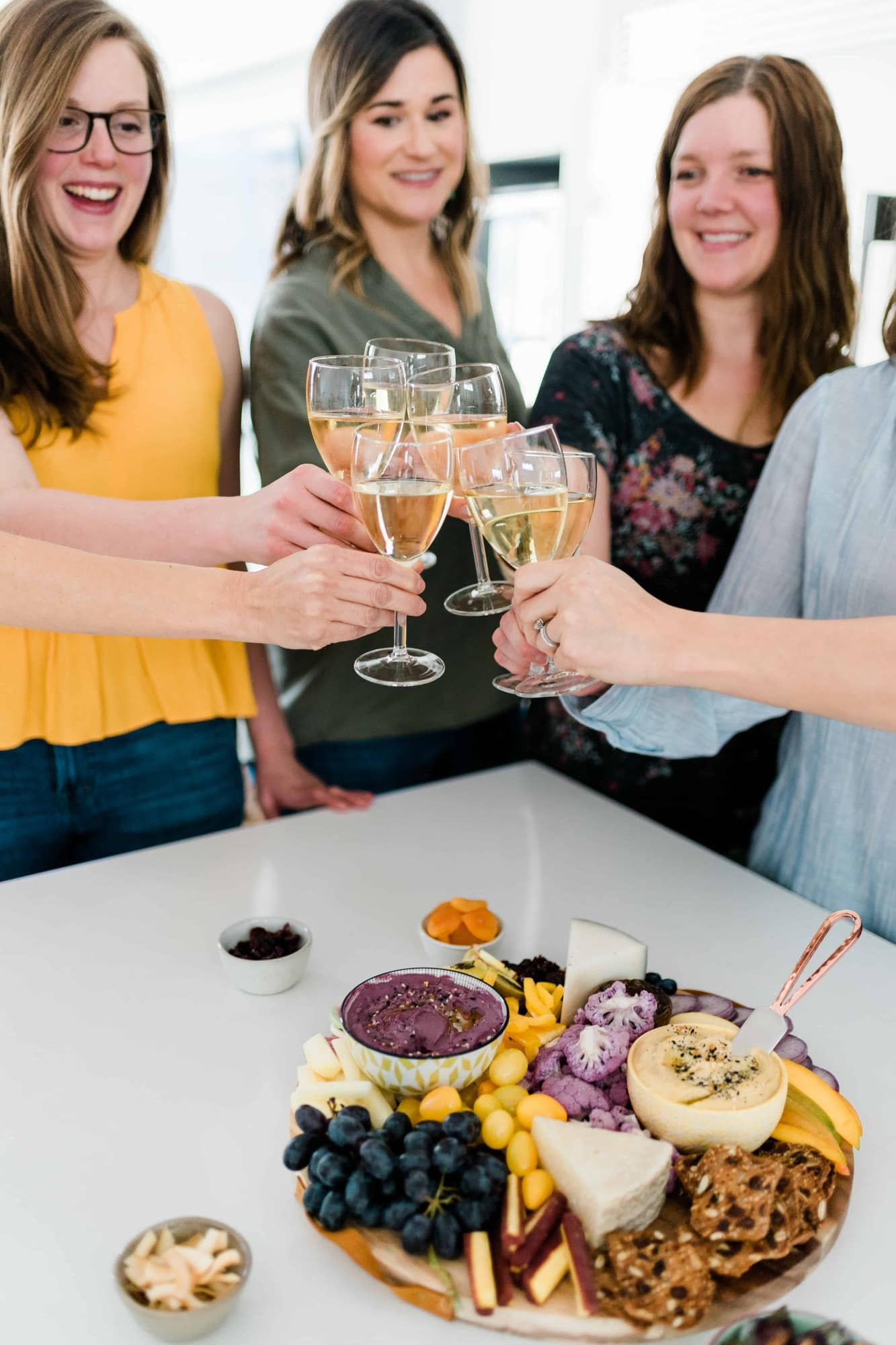 Six women clinking white wine glasses together