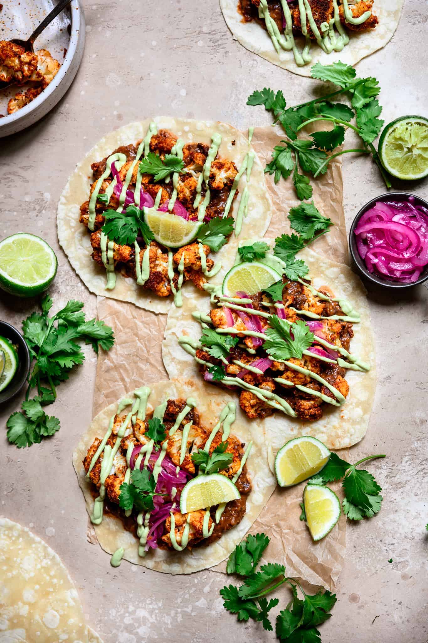 overhead view of tacos with roasted cauliflower, black beans and avocado crema