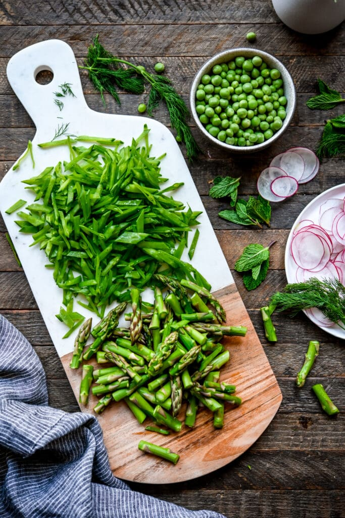 Overhead view of spring vegetables on a white cutting board