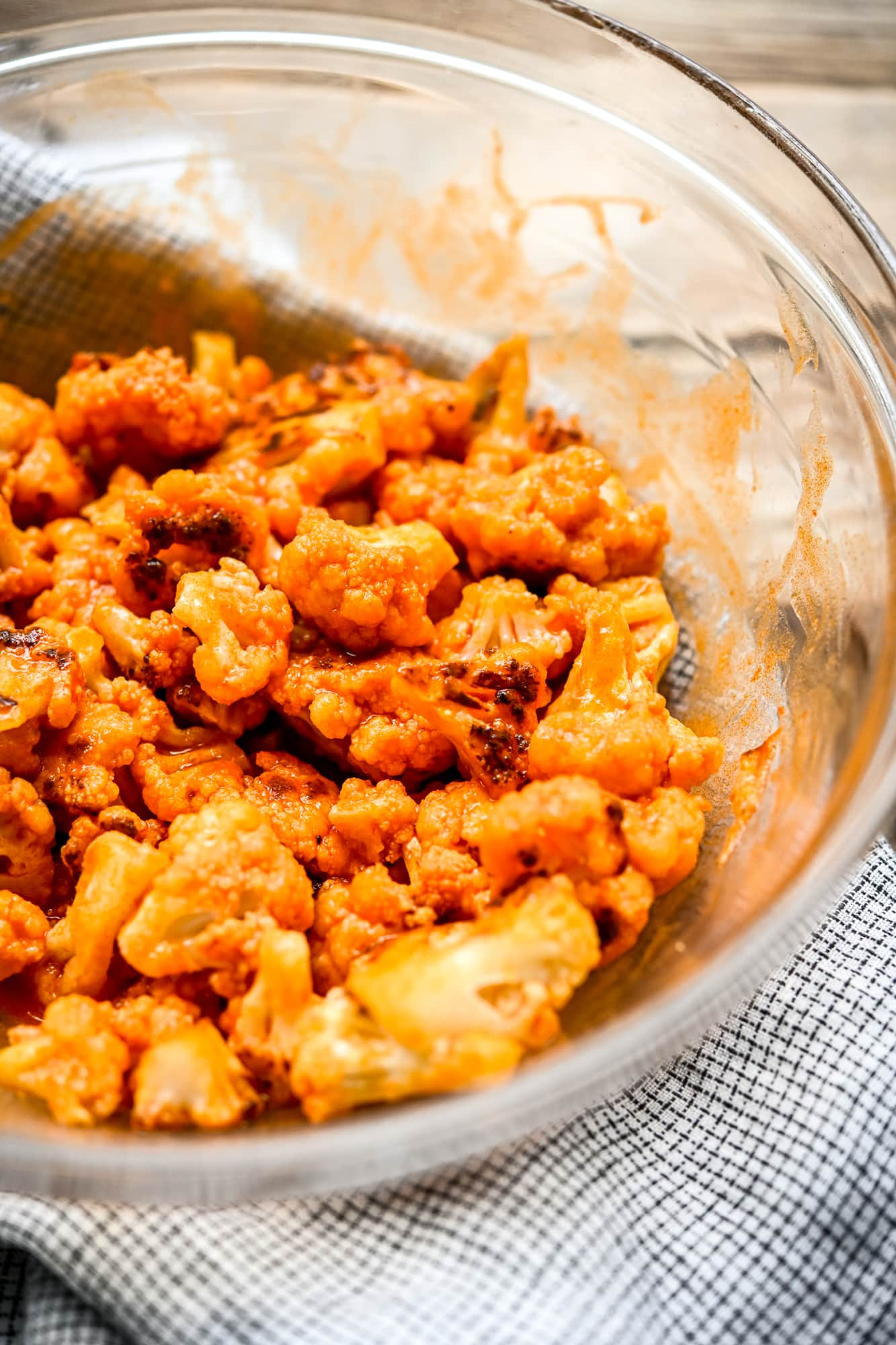 Close up side view of vegan buffalo cauliflower in a glass bowl