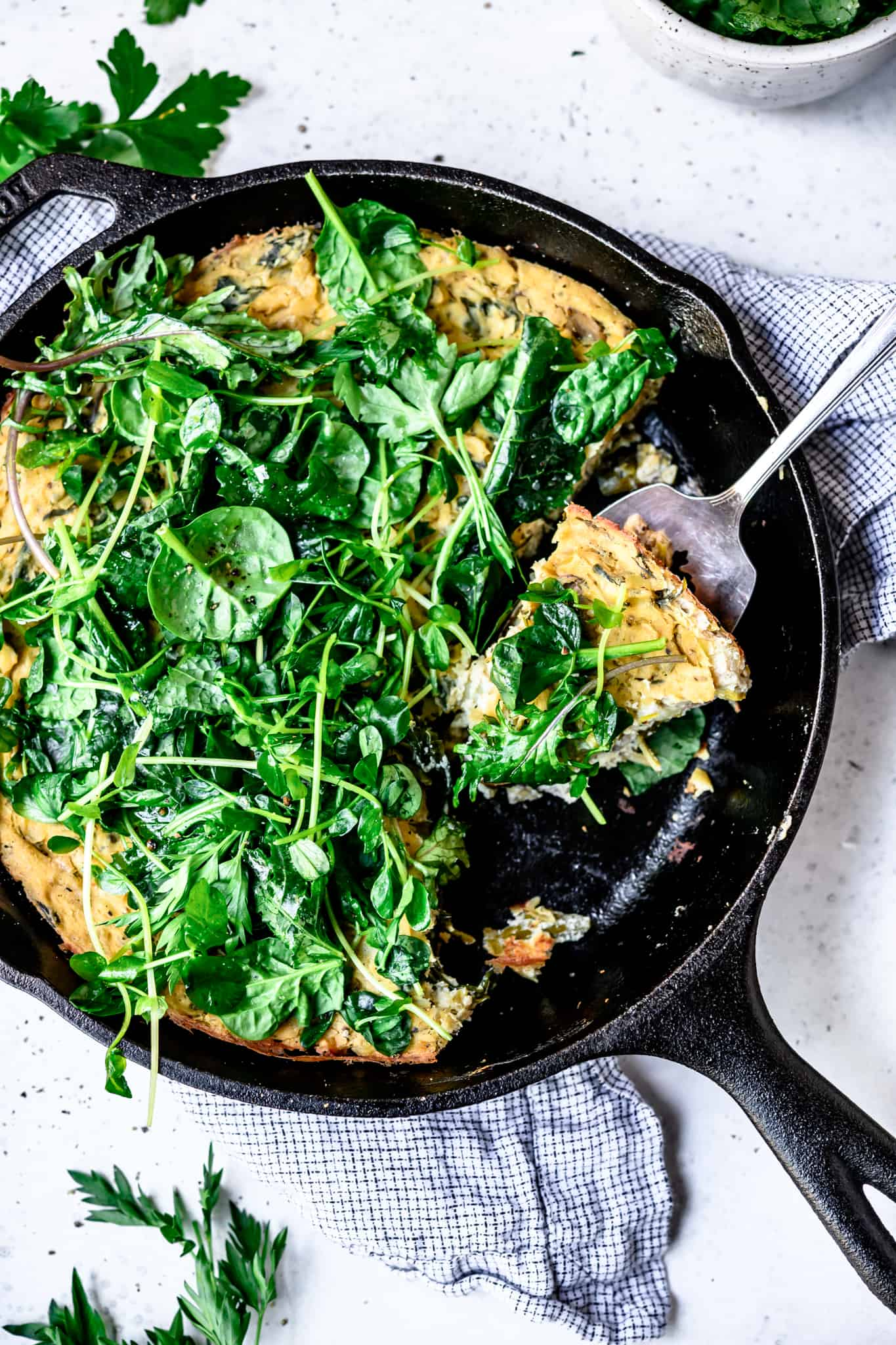 Overhead view of vegan spring vegetable frittata in a cast iron skillet on white background