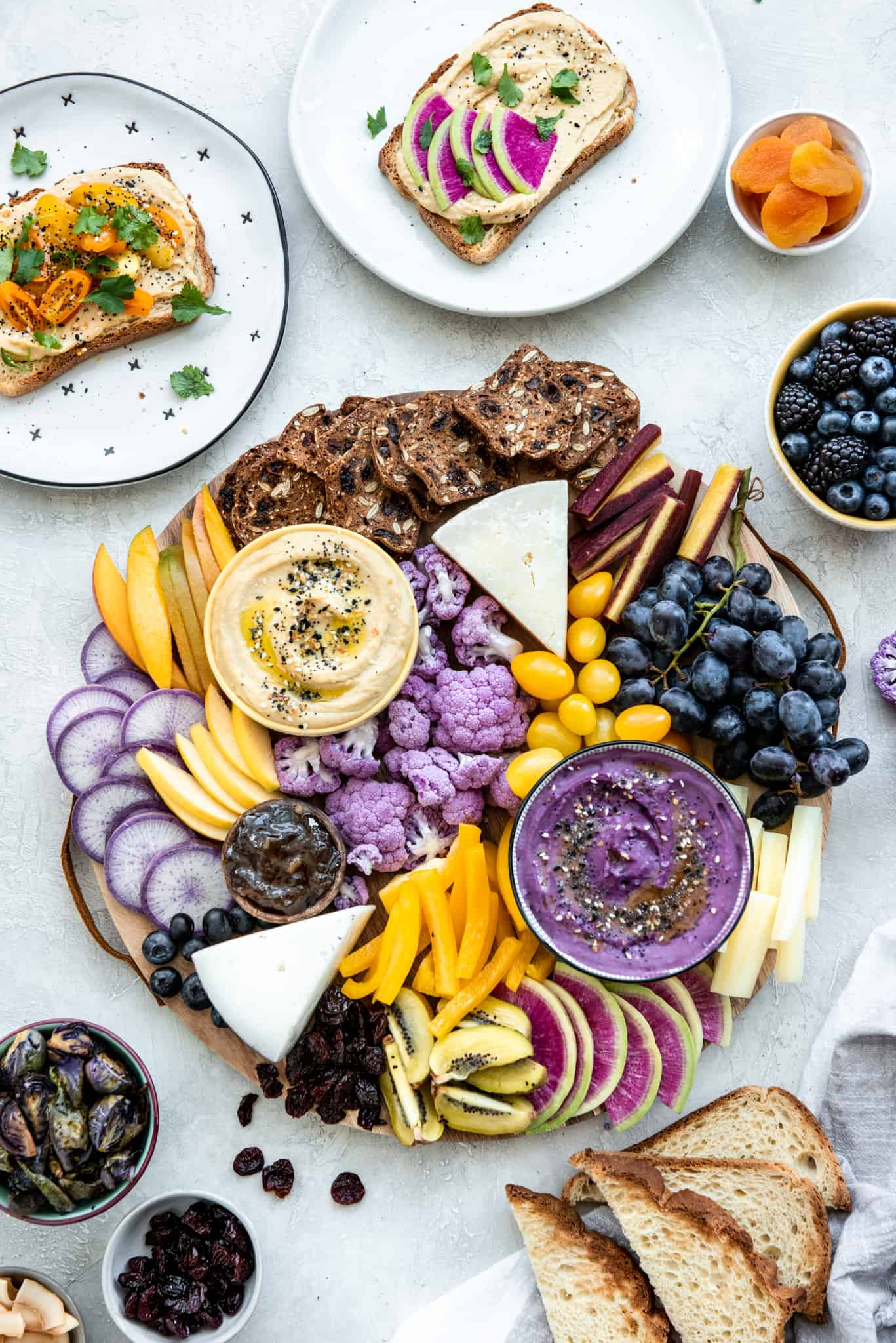 Overhead view of purple and yellow hummus appetizer platter on a gray background