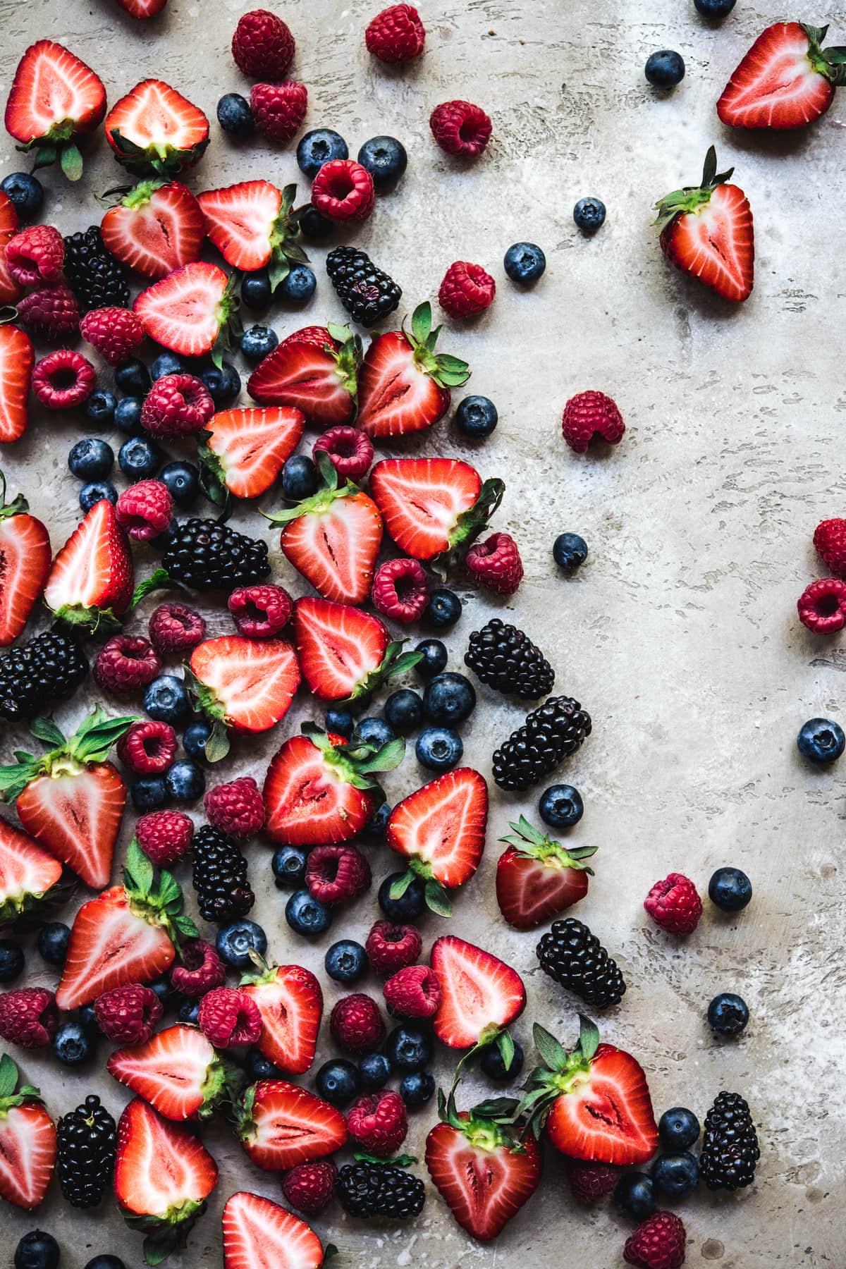 Overhead view of beautiful food photography of fresh blueberries, raspberries, strawberries and blackberries on rustic tan background