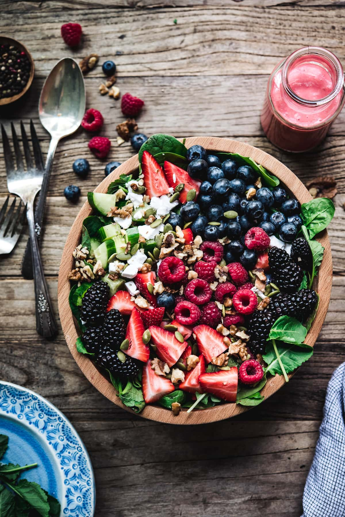 Overhead view of berry spinach salad with feta and cucumbers in wooden bowl