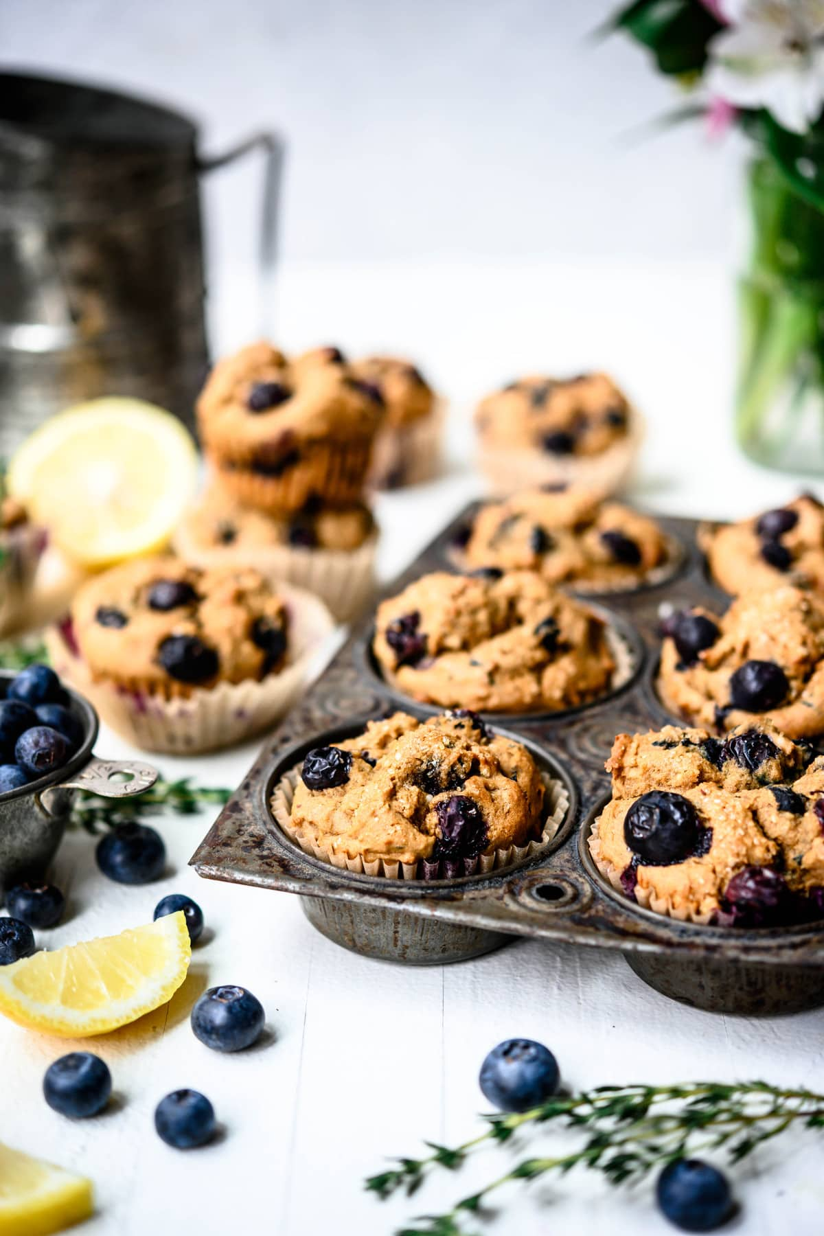 Side view of vegan blueberry lemon muffins in rustic muffin tin on white background