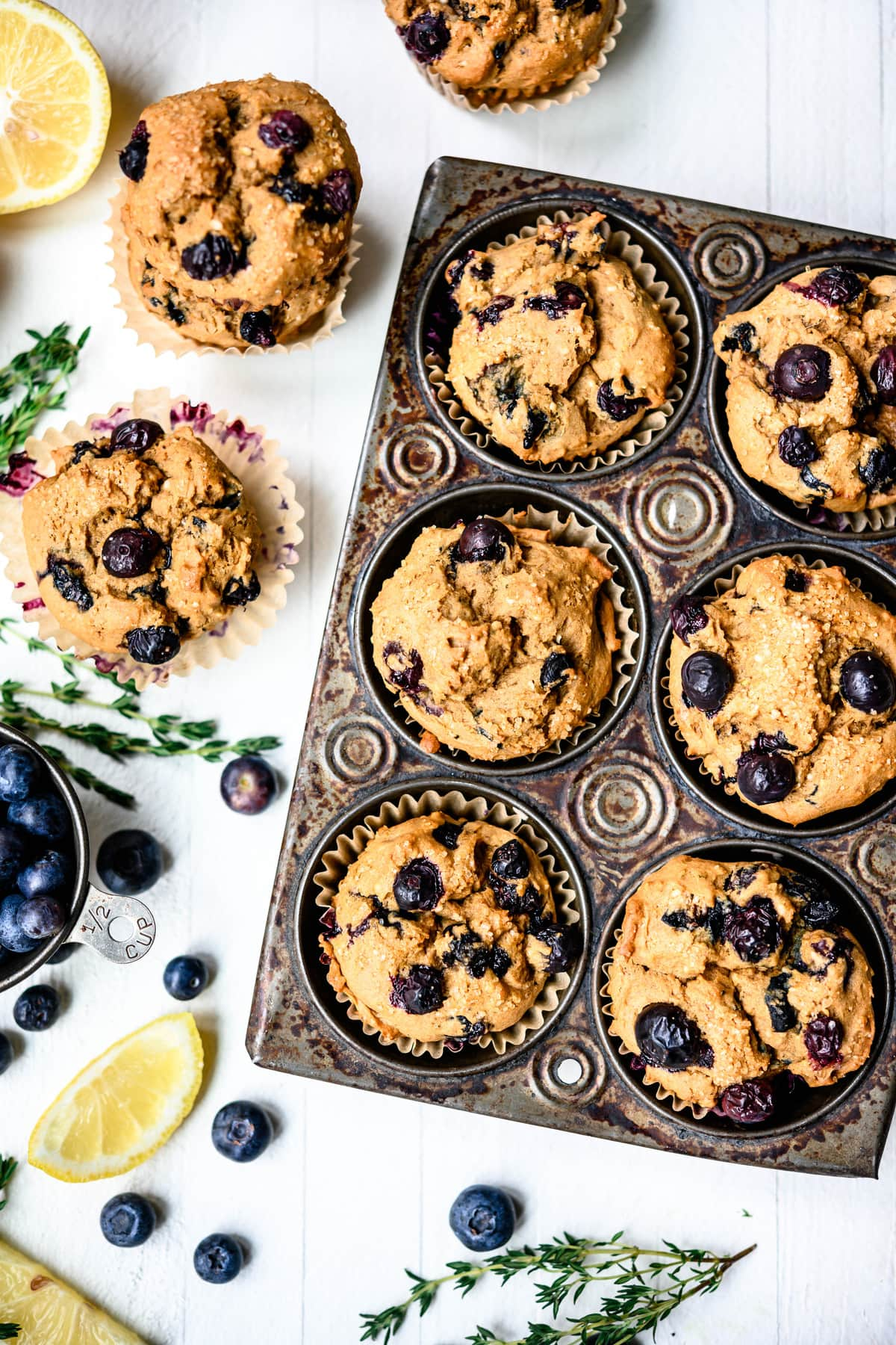 Overhead view of vegan blueberry lemon muffins in rustic muffin tin on white background