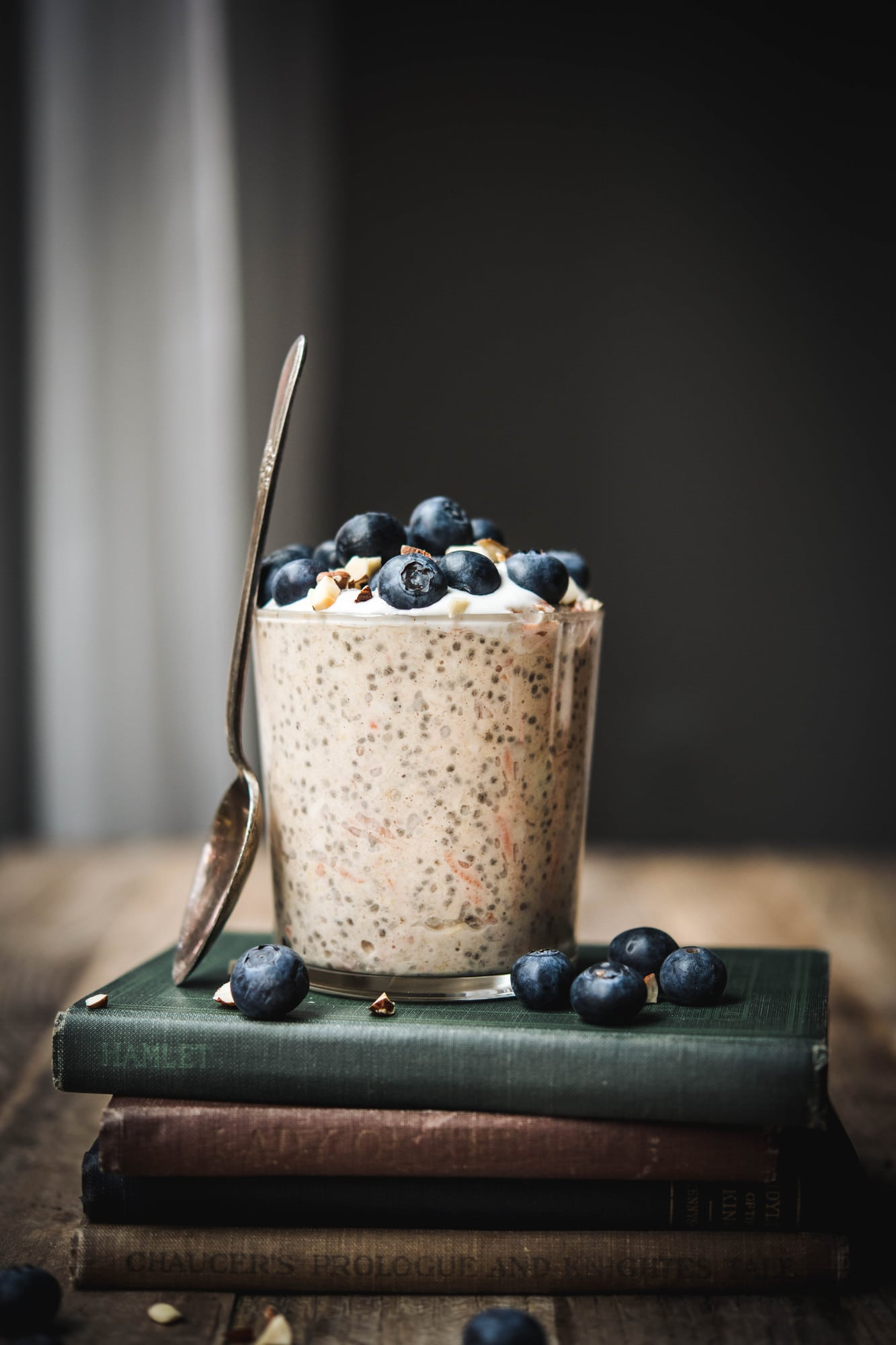 Side view of carrot cake overnight oats in a glass jar topped with blueberries on a stack of antique books