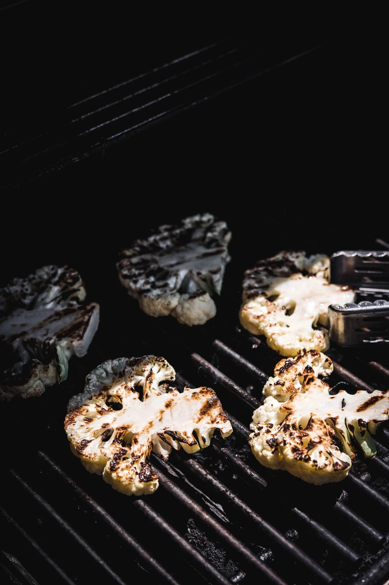 Side view of cauliflower steaks on a grill in sunshine
