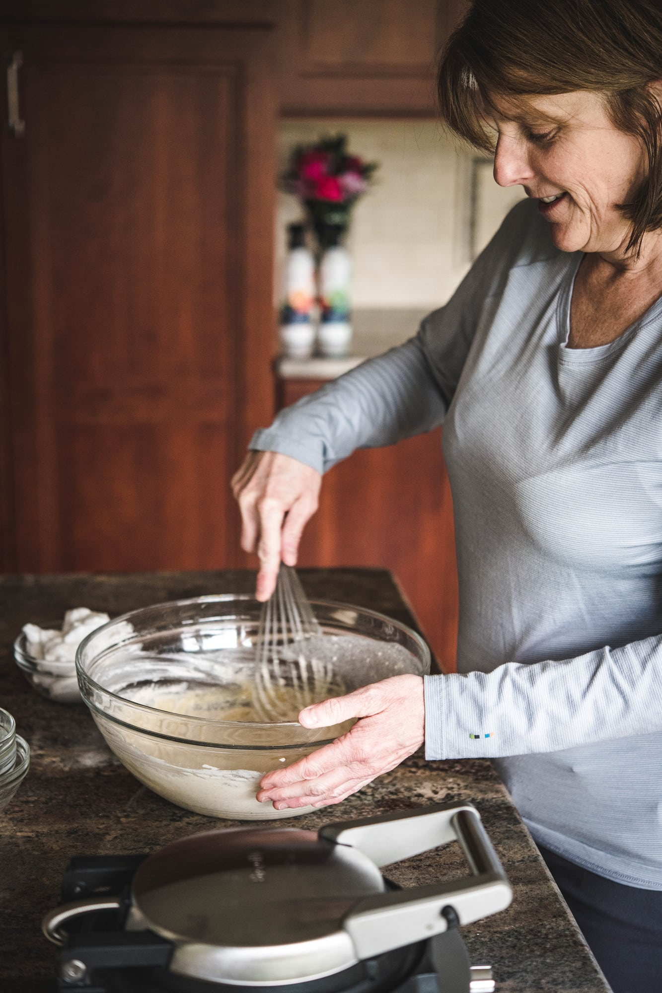 Woman whisking waffle batter in large glass bowl