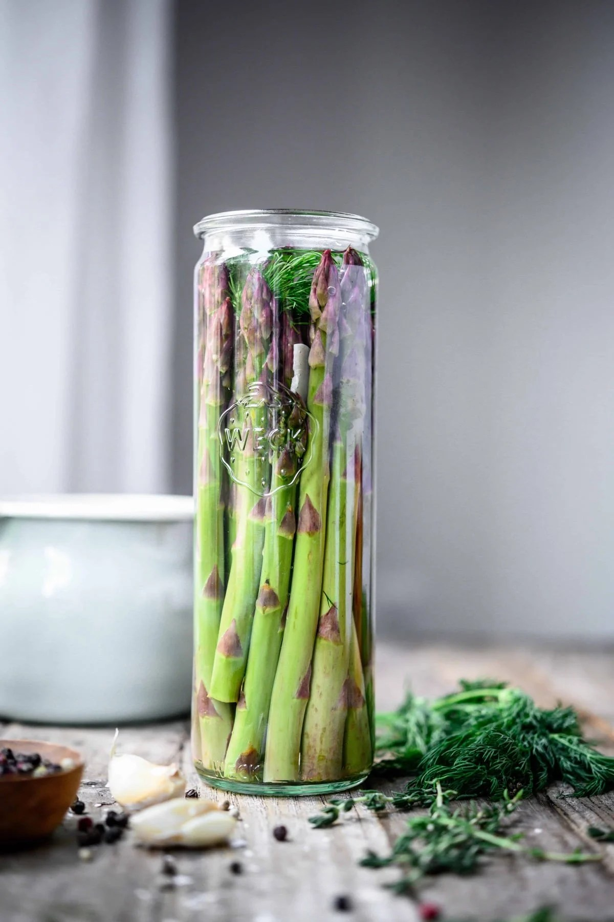 Side view of tall glass jar of dill pickled asparagus