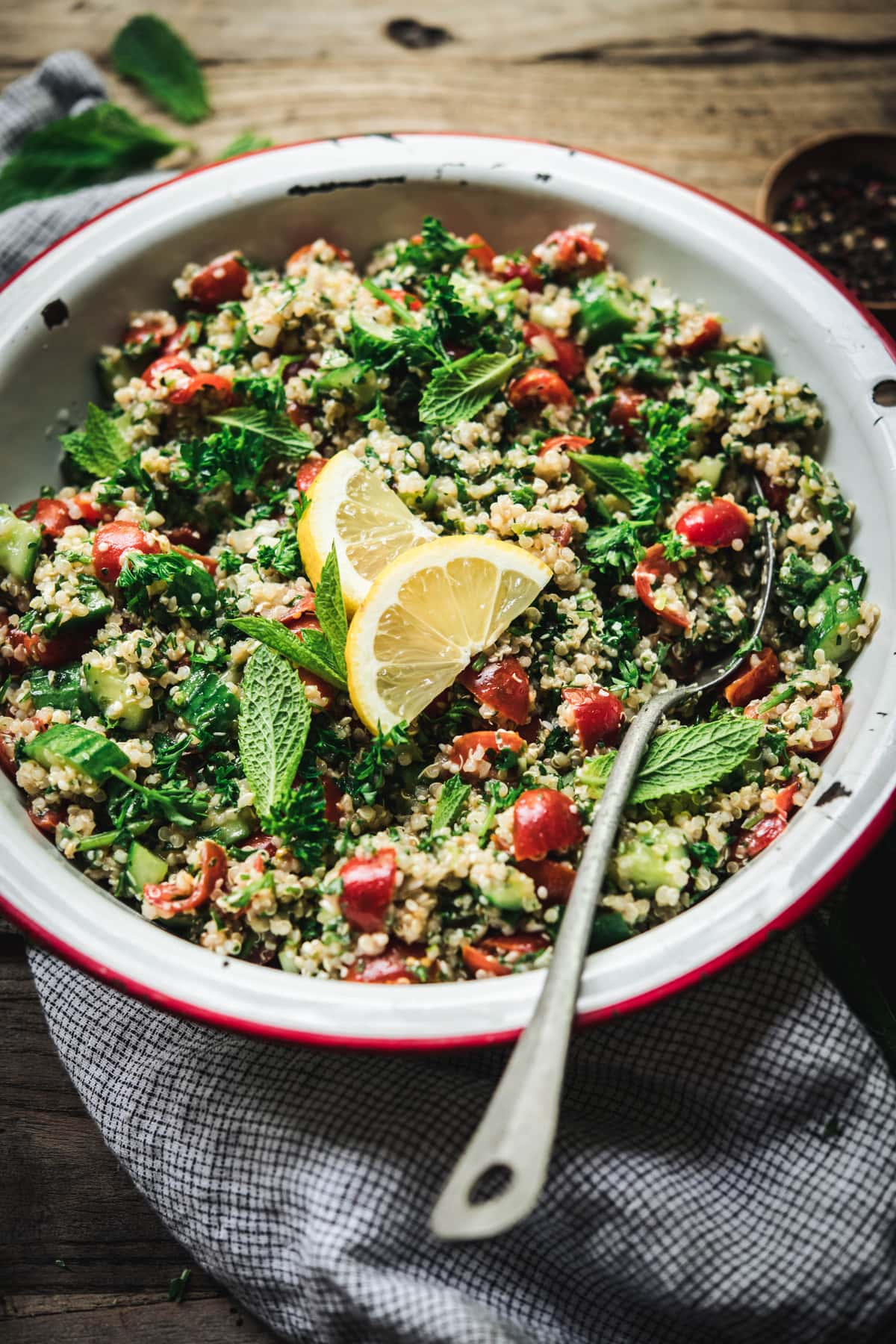 Side view of quinoa tabbouleh in a white and red enamel bowl on wood table