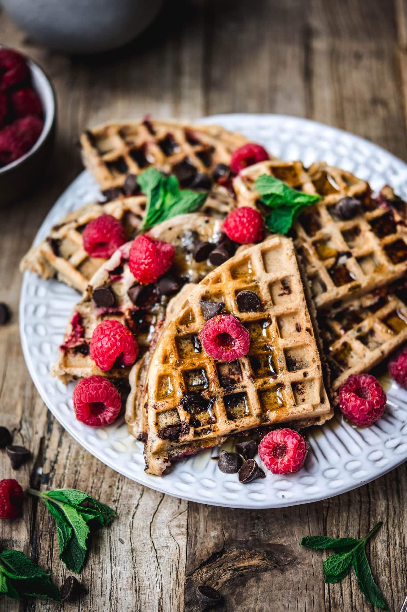Side view of raspberry chocolate chip waffles on white plate