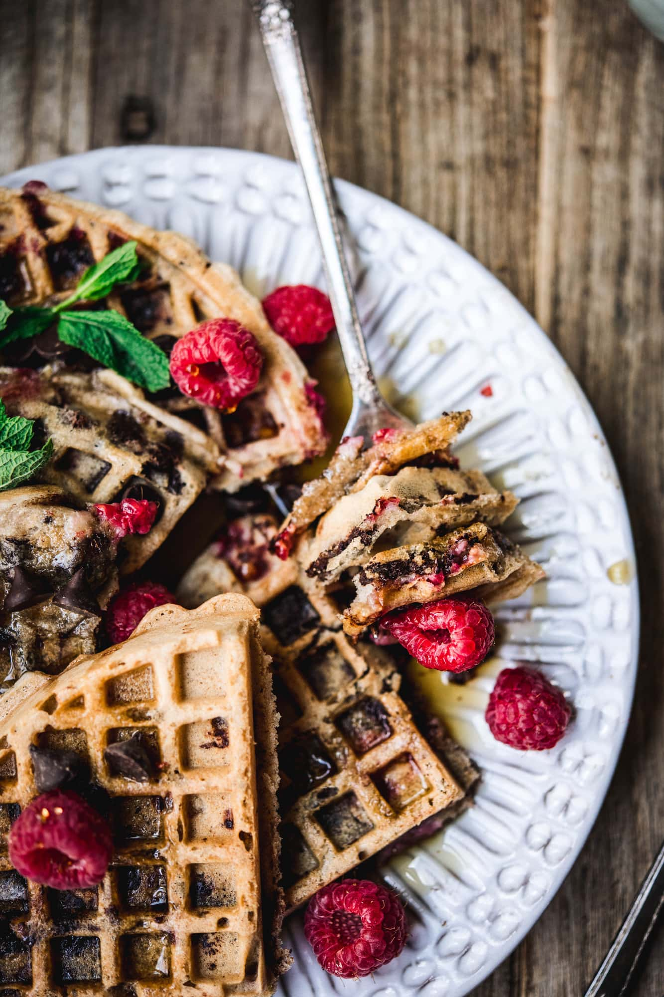 side view of raspberry chocolate chip waffles on plate