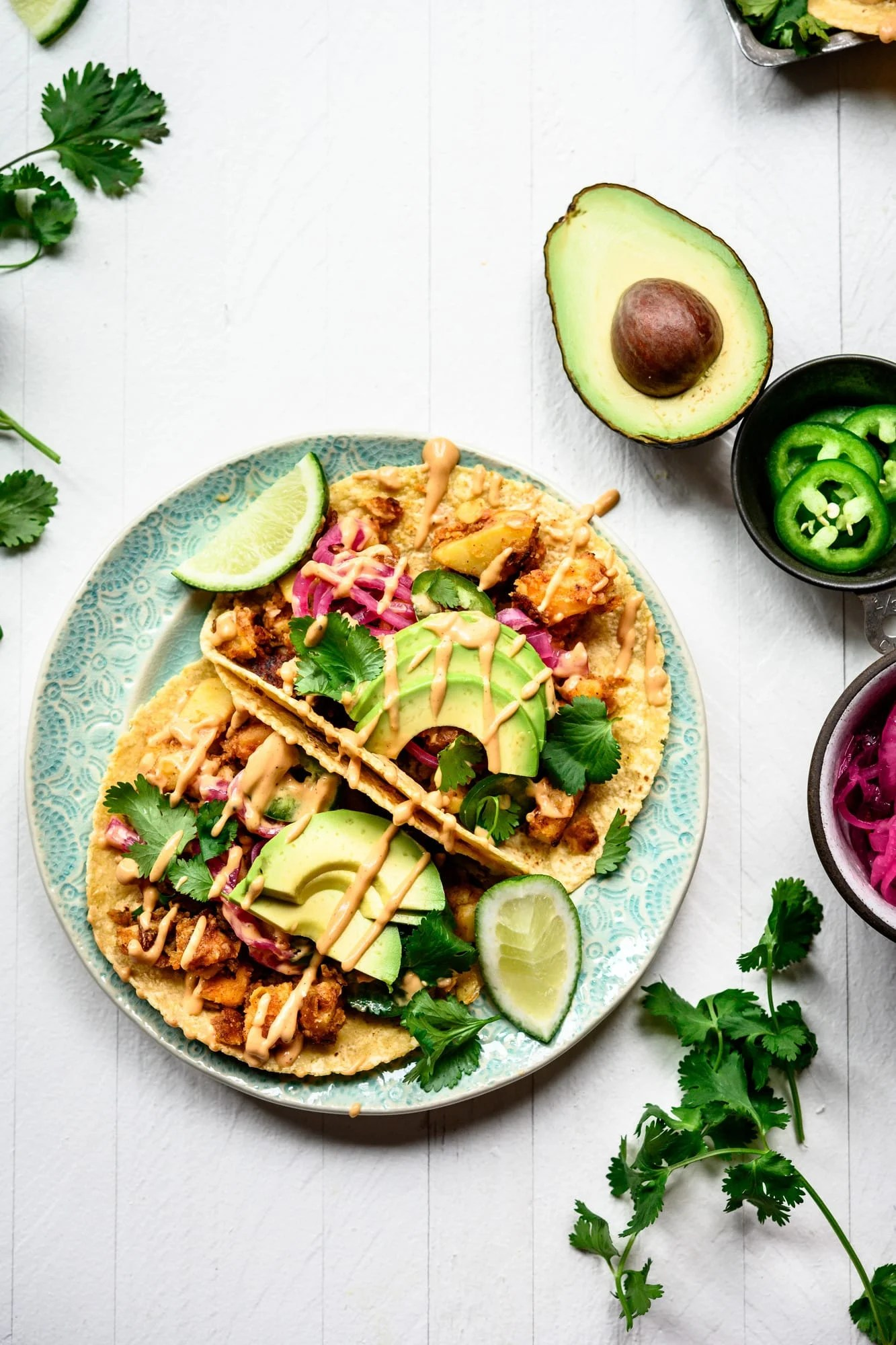 Overhead view of two vegan breakfast potato tacos on a teal plate with avocados and spicy mayo