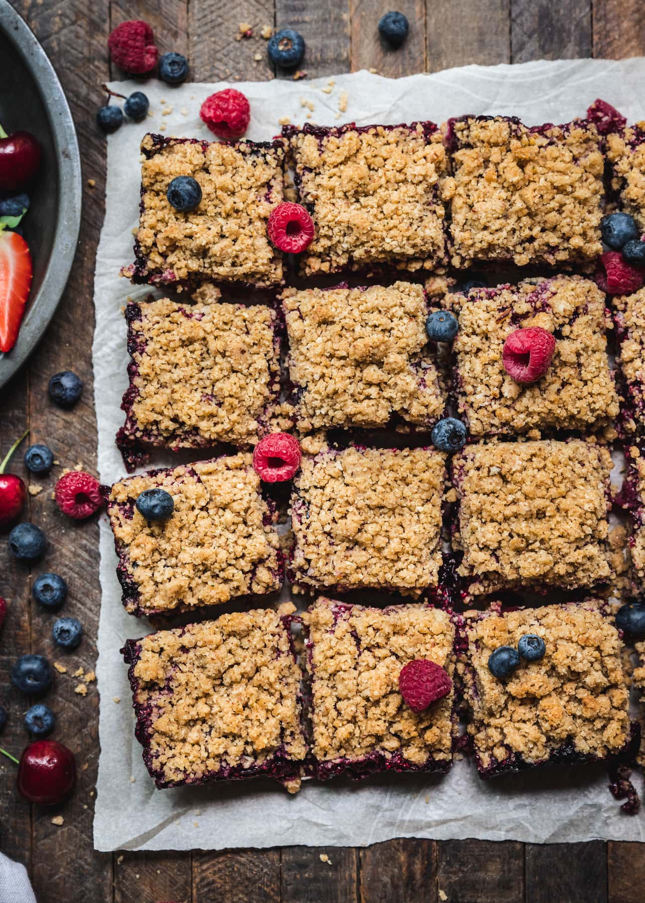 overhead of vegan four berry pie bars cut into squares on a baking sheet