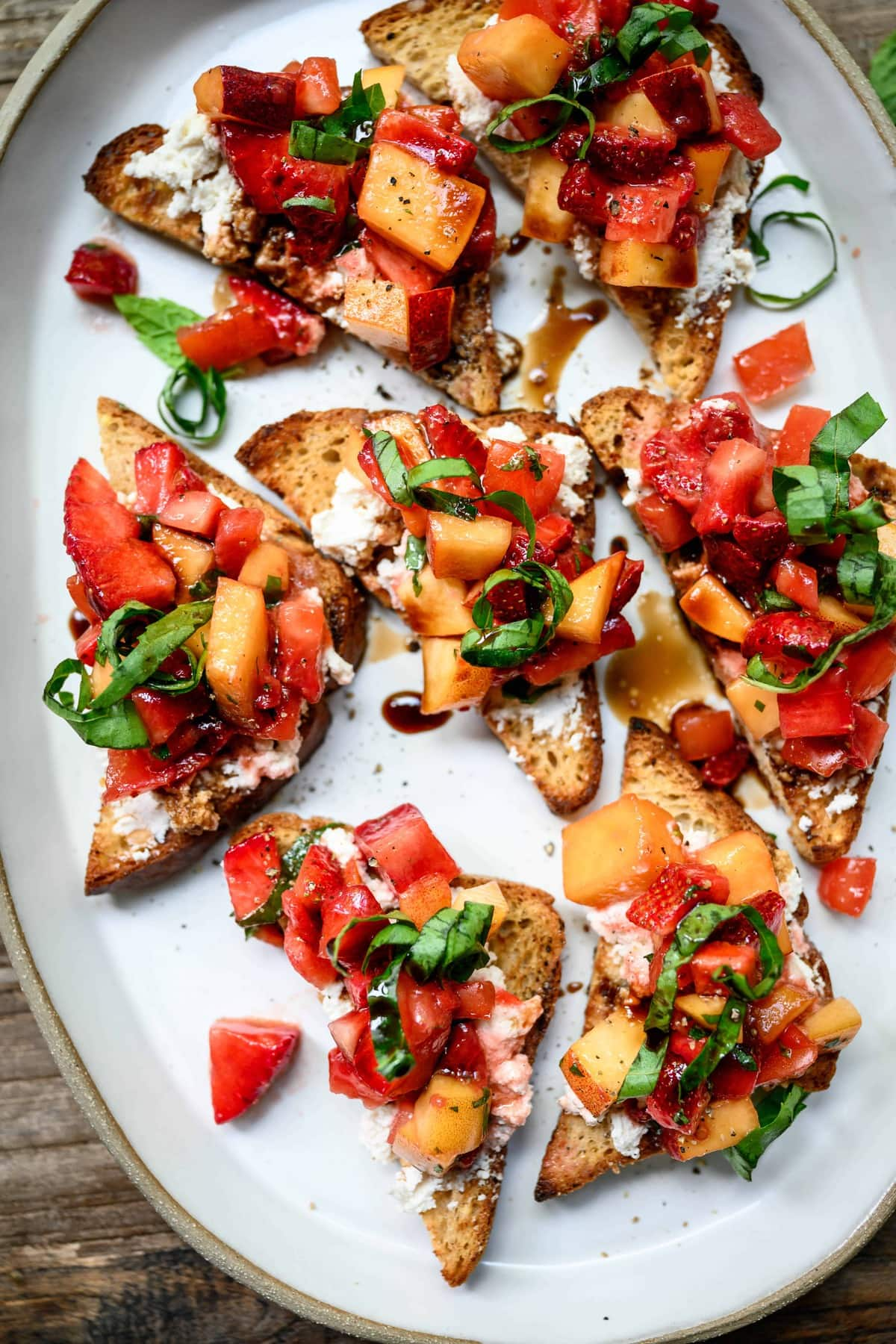 close up overhead view of strawberry peach bruschetta on a white ceramic platter on wood table with white wine
